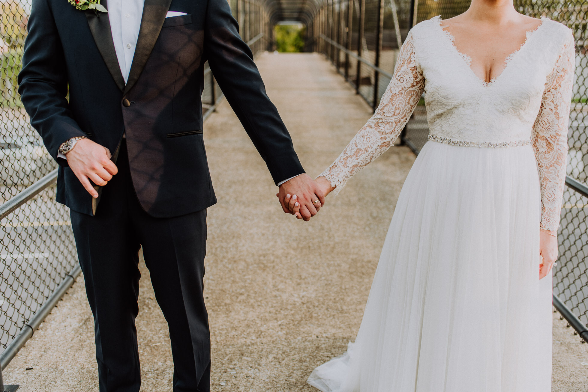 bride and groom holding hands on overpass in nashville tennessee