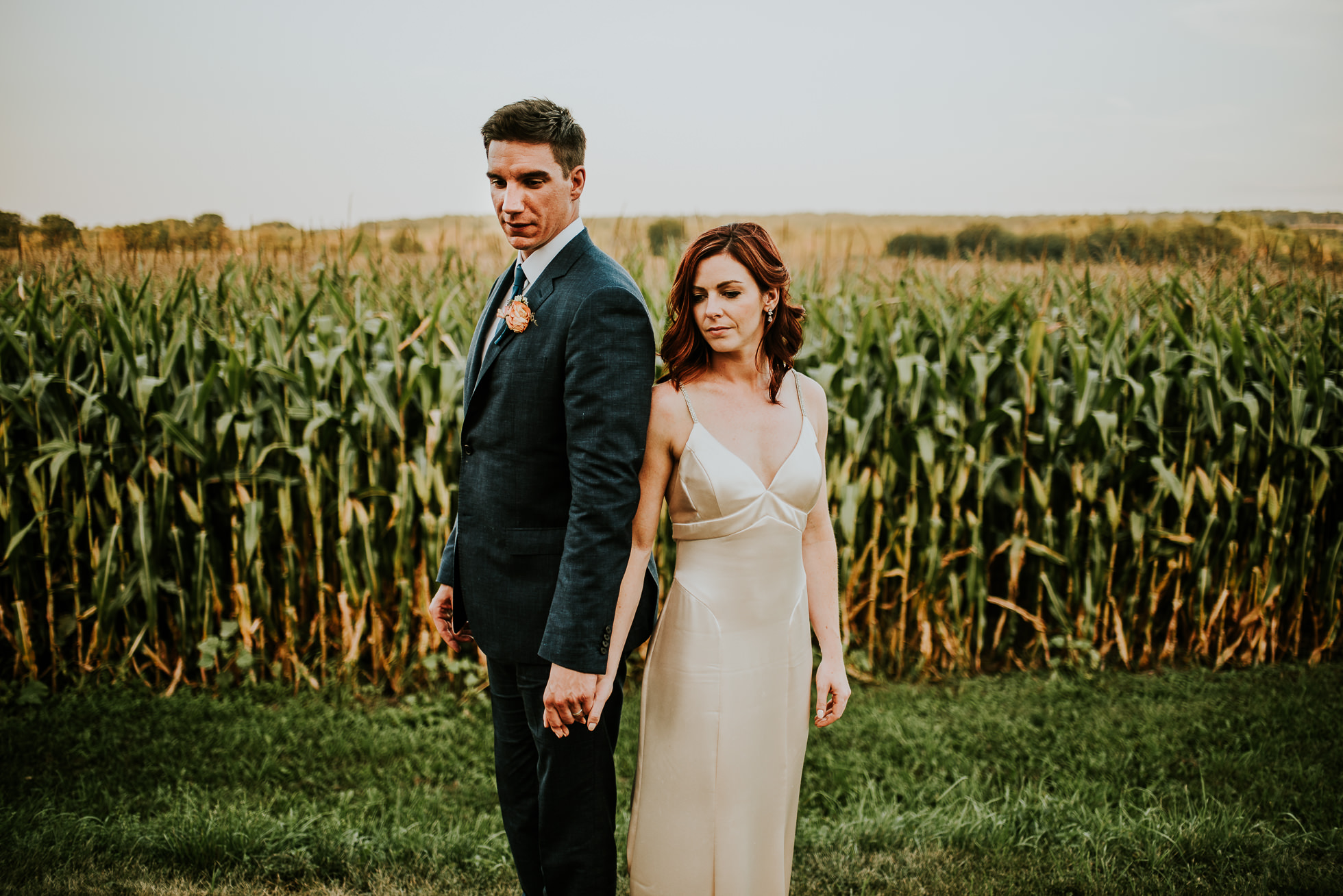 bride and groom holding hands near corn field at olde tater barn wedding in central bridge, ny photographed by traverse the tides