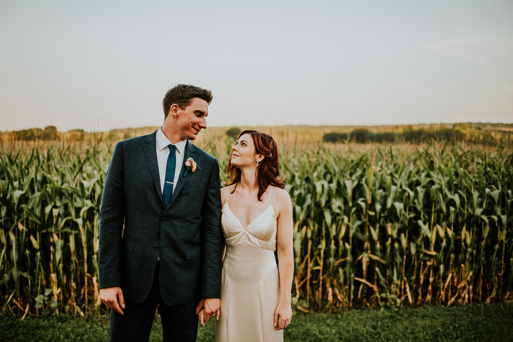 bride and groom looking at each other near corn field at olde tater barn wedding in central bridge, ny photographed by traverse the tides