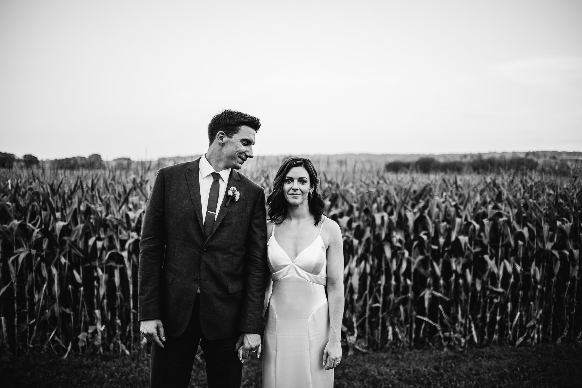 black and white wedding portait near corn field at olde tater barn wedding in central bridge, ny photographed by traverse the tides