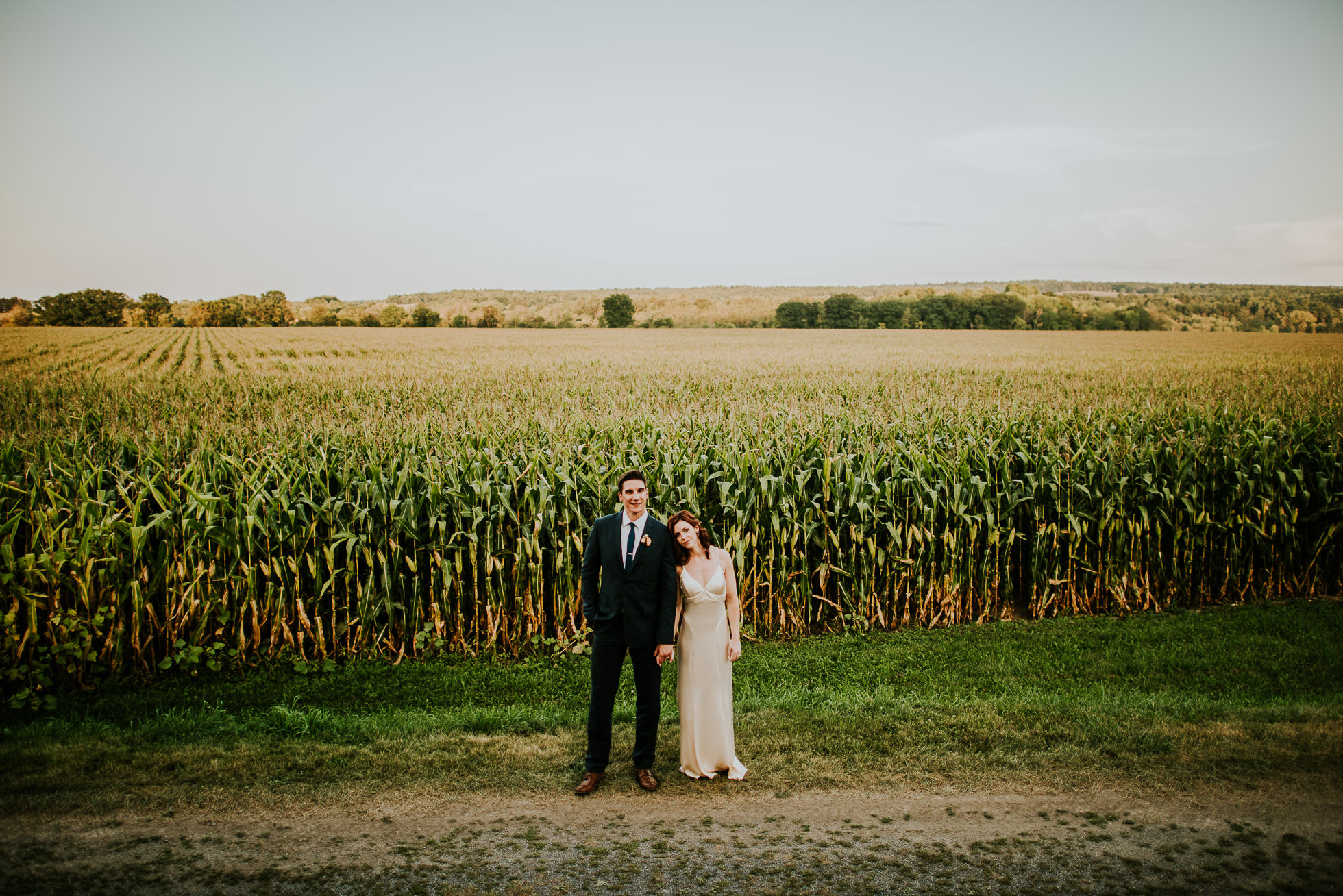bride and groom wide portrait near corn field at olde tater barn wedding in central bridge, ny photographed by traverse the tides
