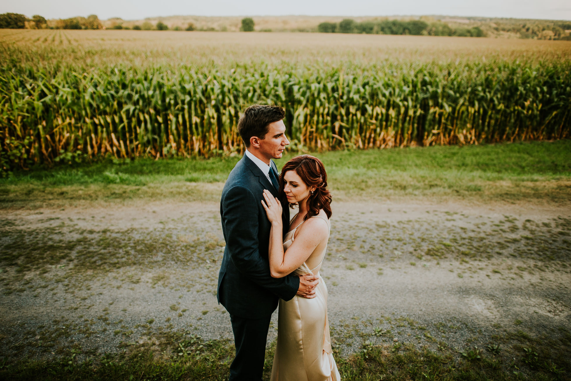bride and groom hugging near corn field at olde tater barn wedding in central bridge, ny photographed by traverse the tides