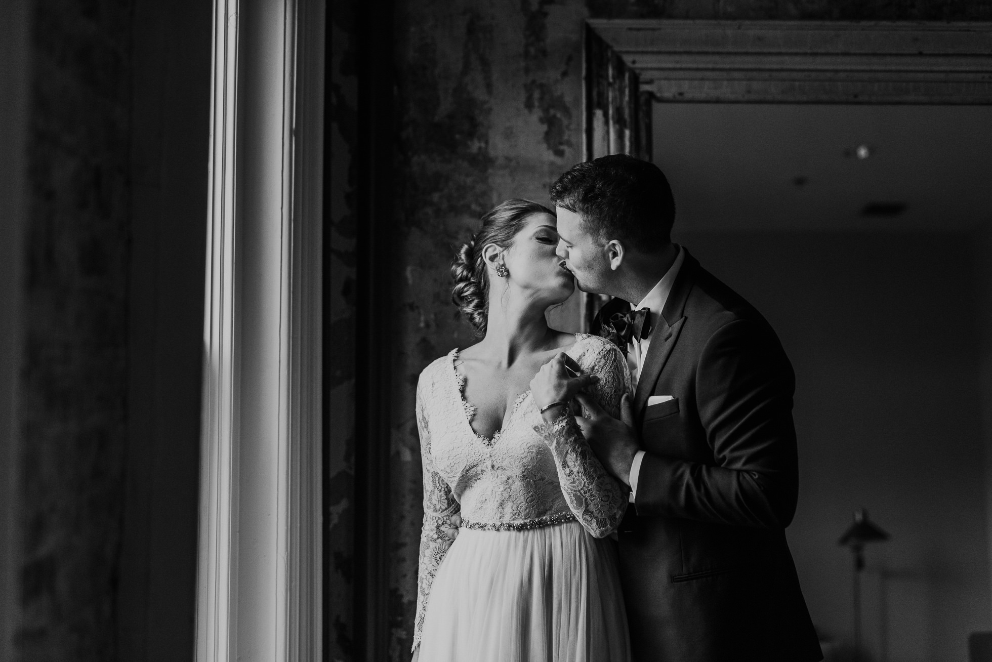 bride and groom kiss by window at the cordelle nashville
