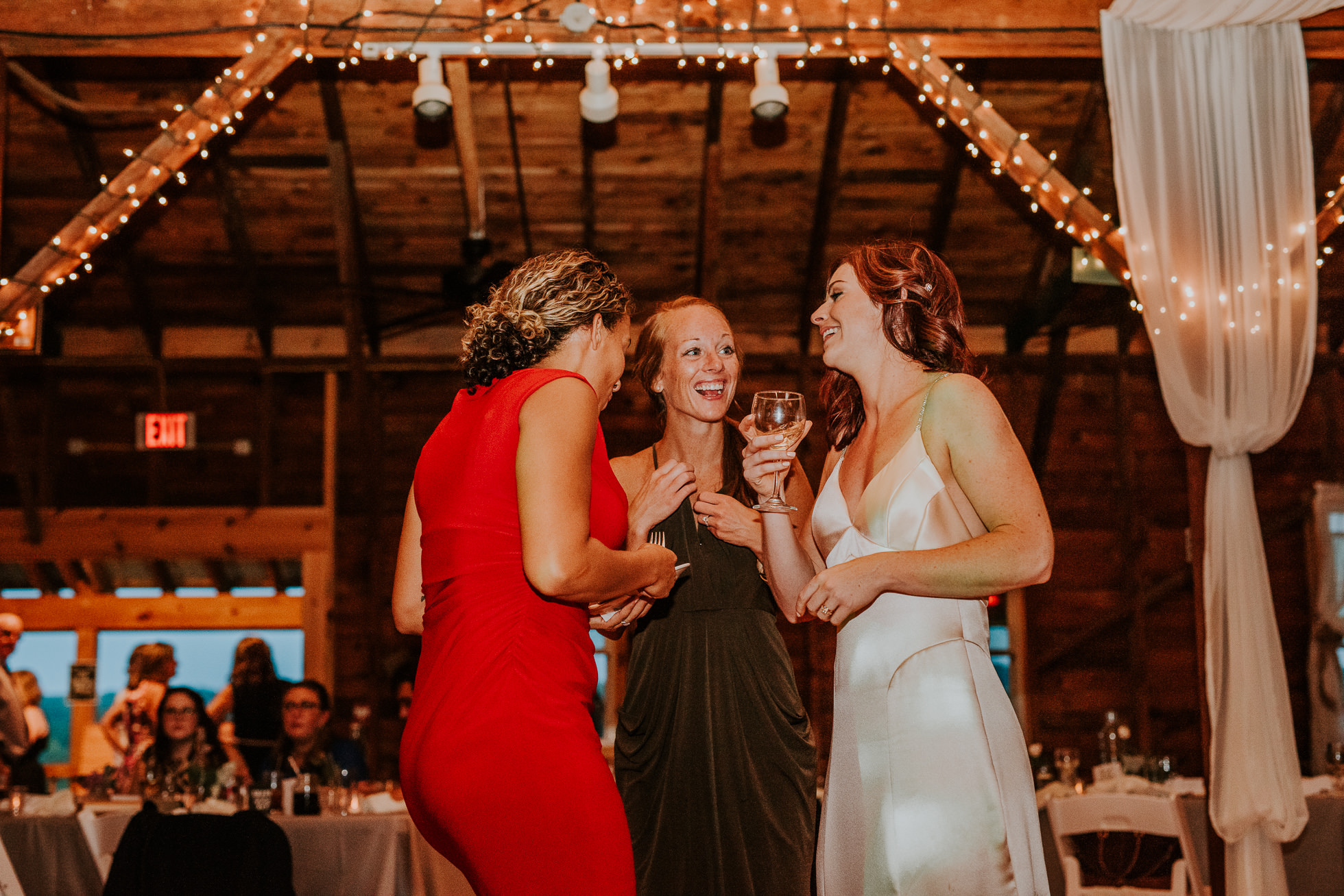 bride and friends laughing at reception at olde tater barn wedding in central bridge, ny photographed by traverse the tides