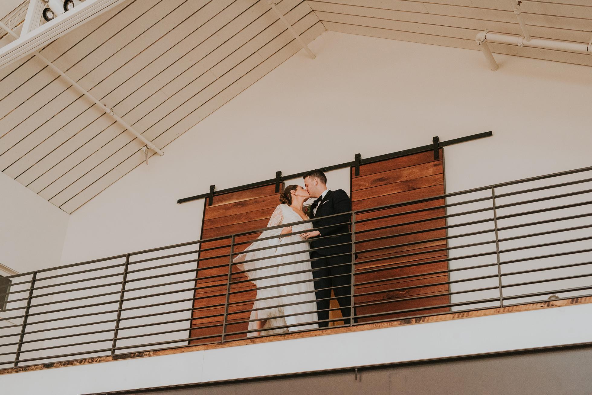 bride and groom kiss on balcony at the cordelle nashville