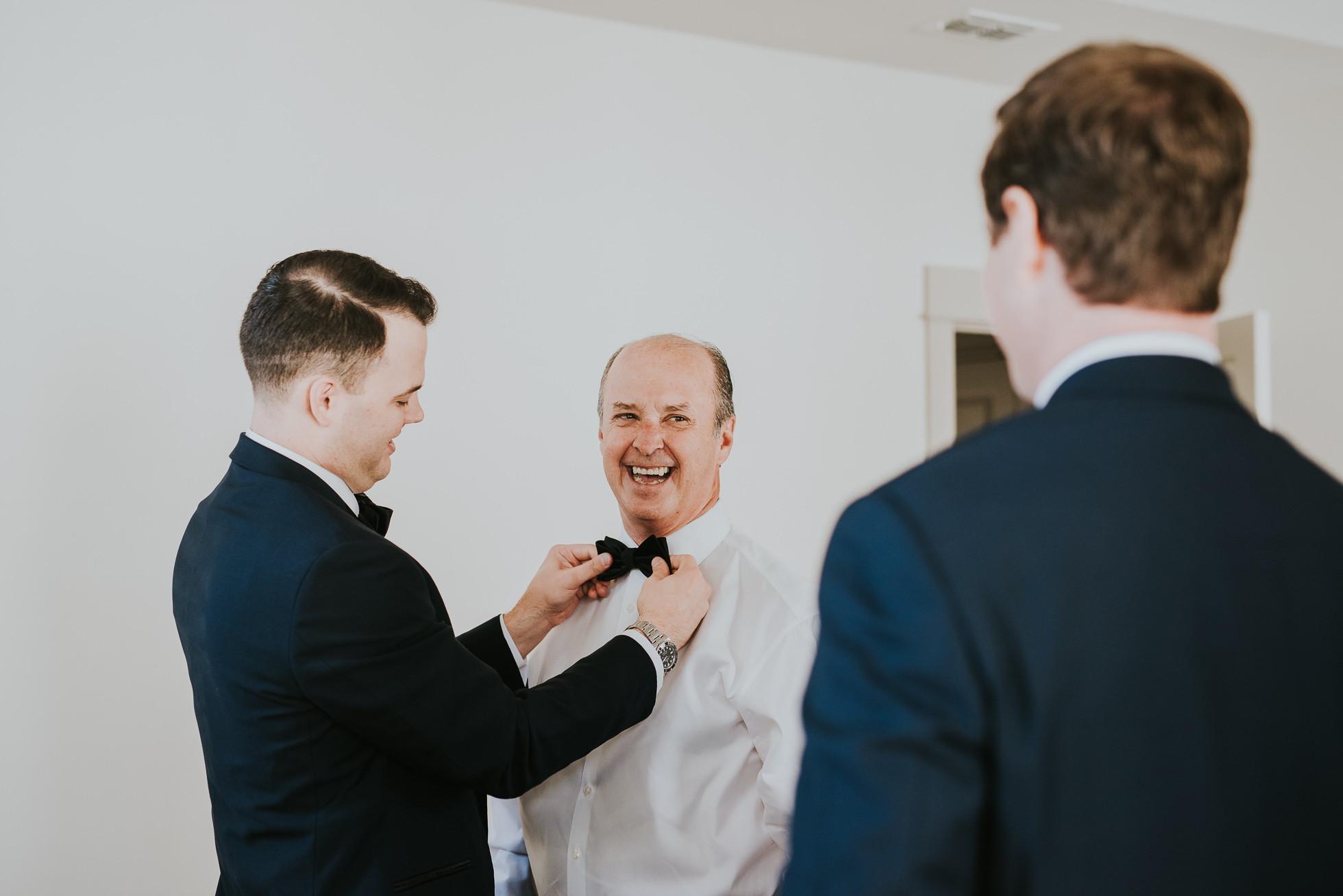 groom tying bowtie for dad