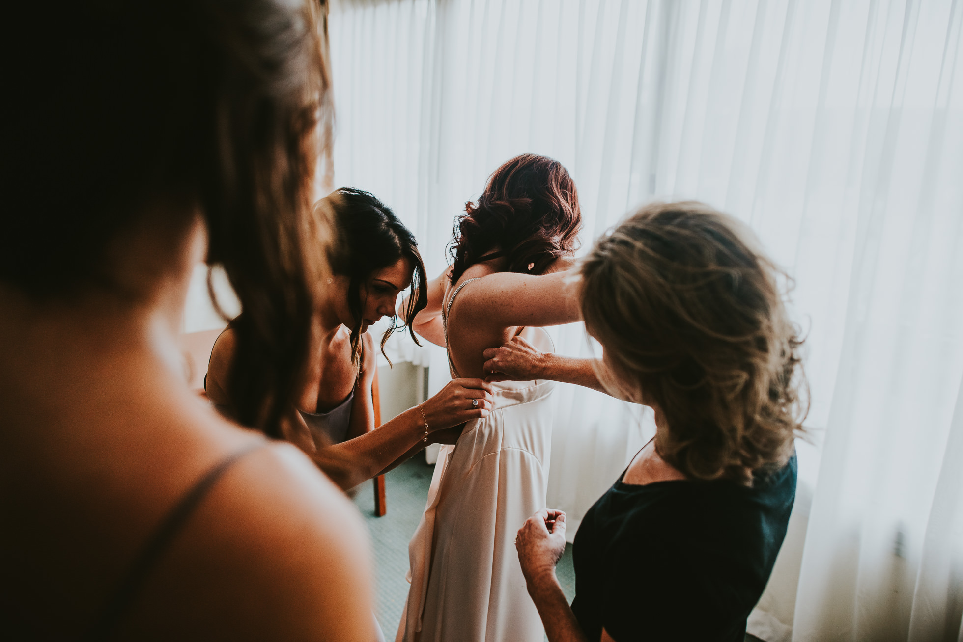 bride getting dressed with mom and bridesmaids at olde tater barn wedding in central bridge, ny photographed by traverse the tides