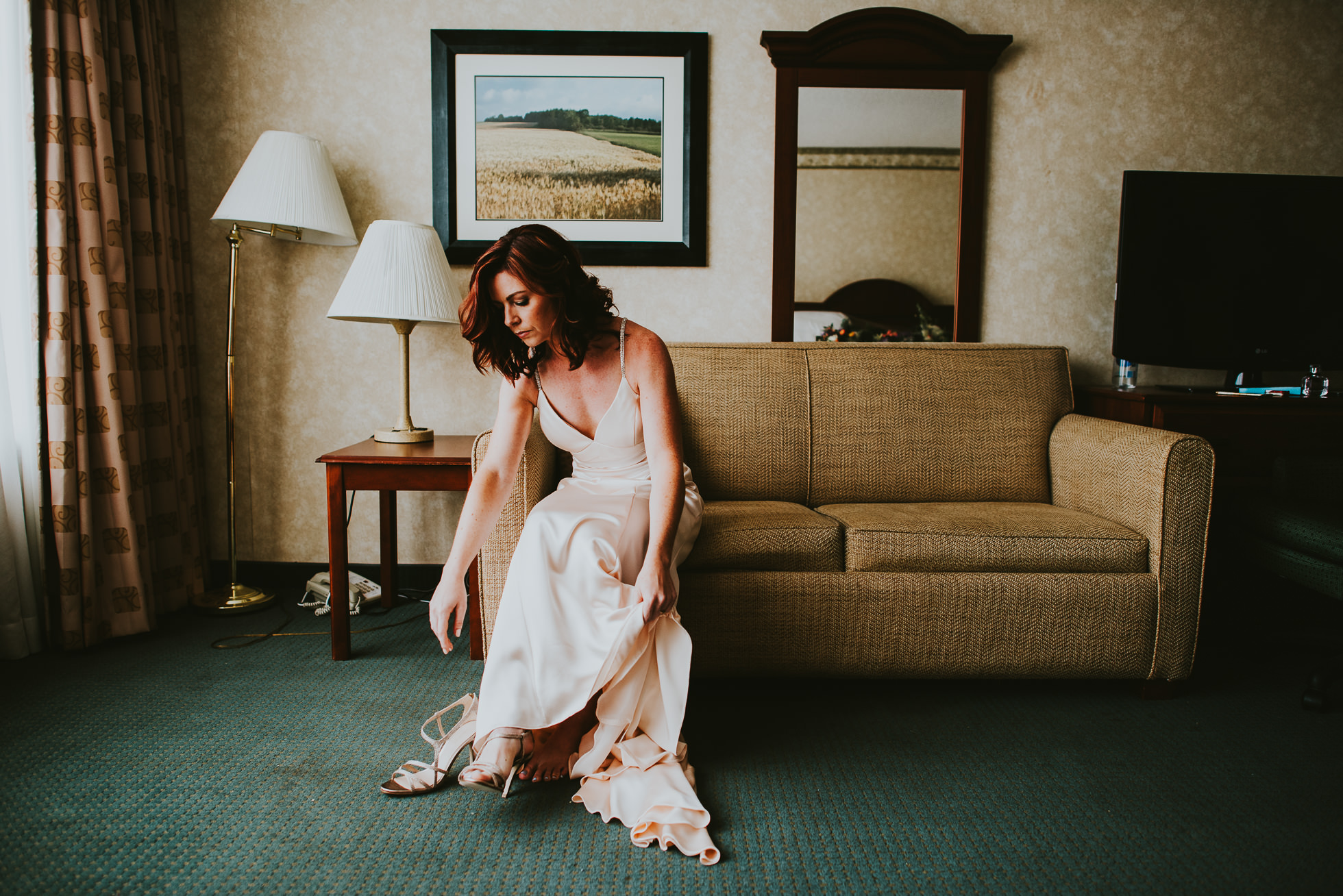 bride putting wedding shoes on at olde tater barn wedding in central bridge, ny photographed by traverse the tides