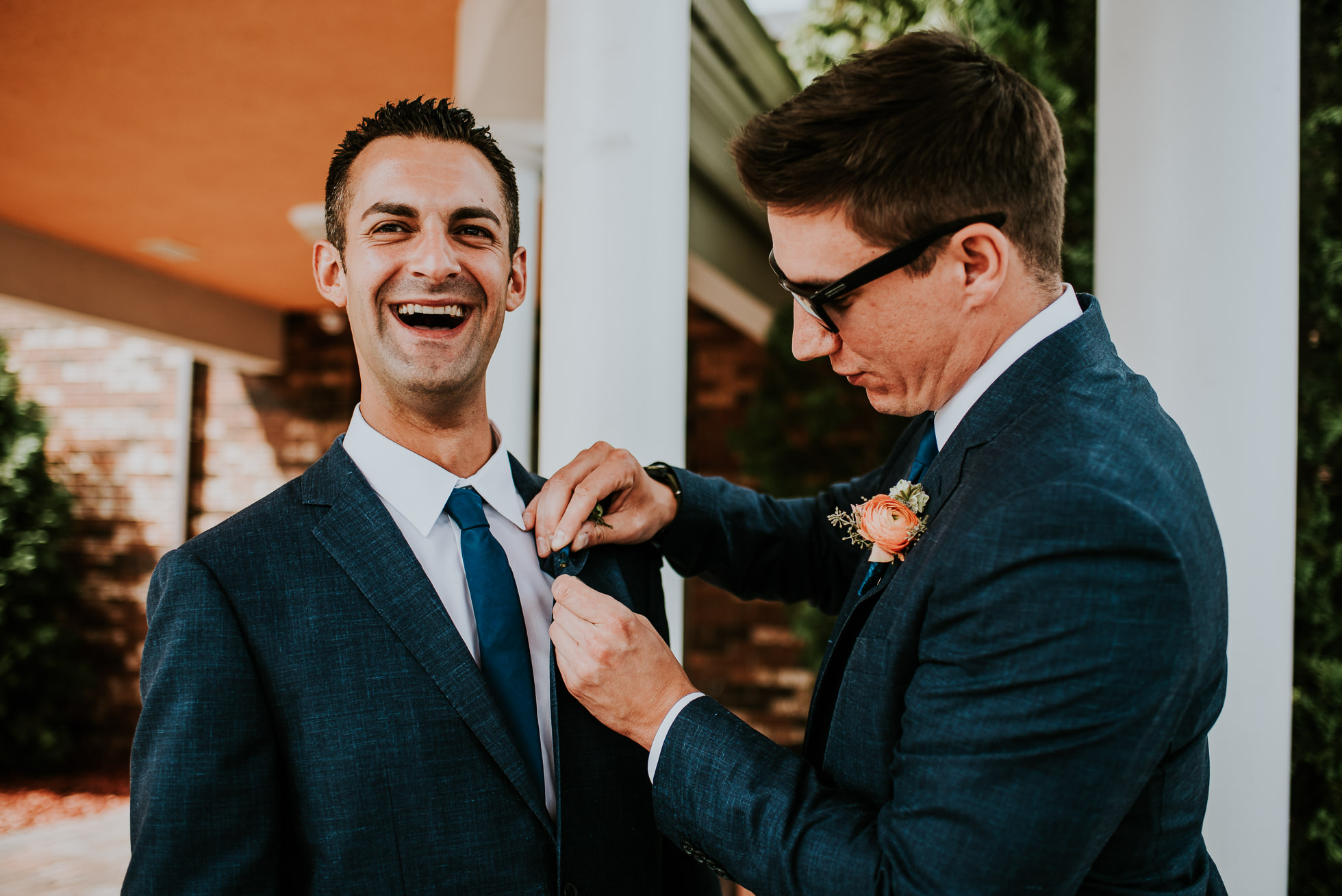 groom putting boutonniere on at olde tater barn wedding in central bridge, ny photographed by traverse the tides