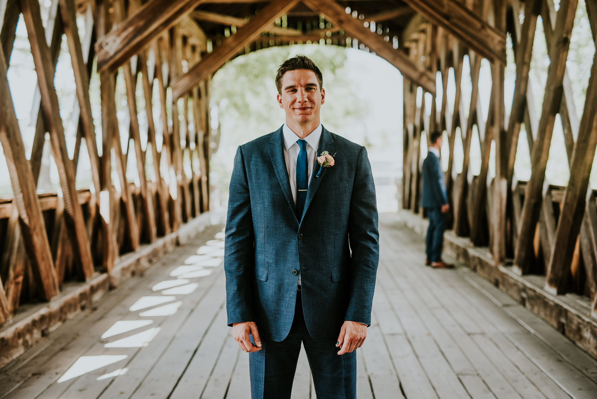 groom on bridge at first look at olde tater barn wedding in central bridge, ny photographed by traverse the tides