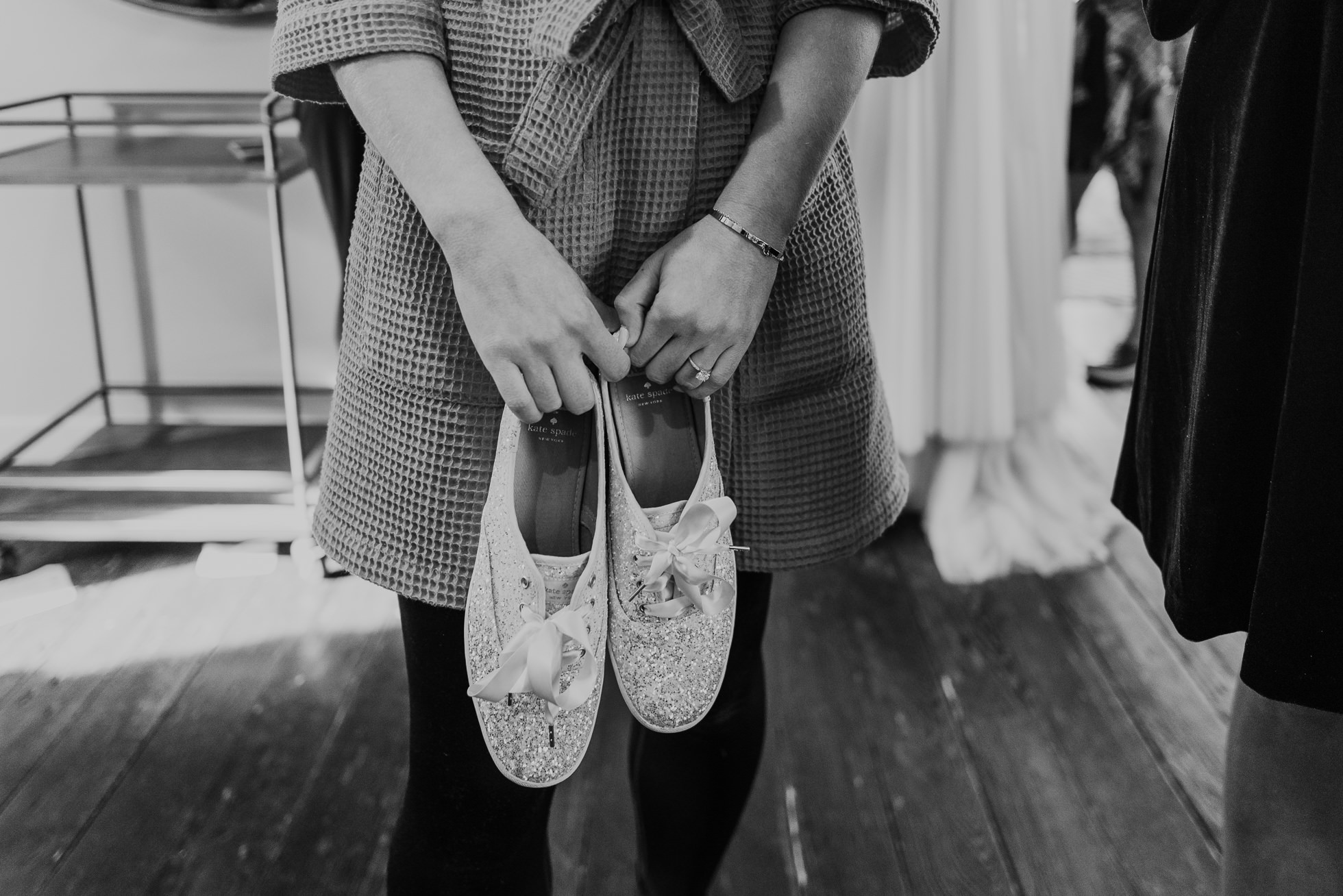 bride holding keds shoes the cordelle