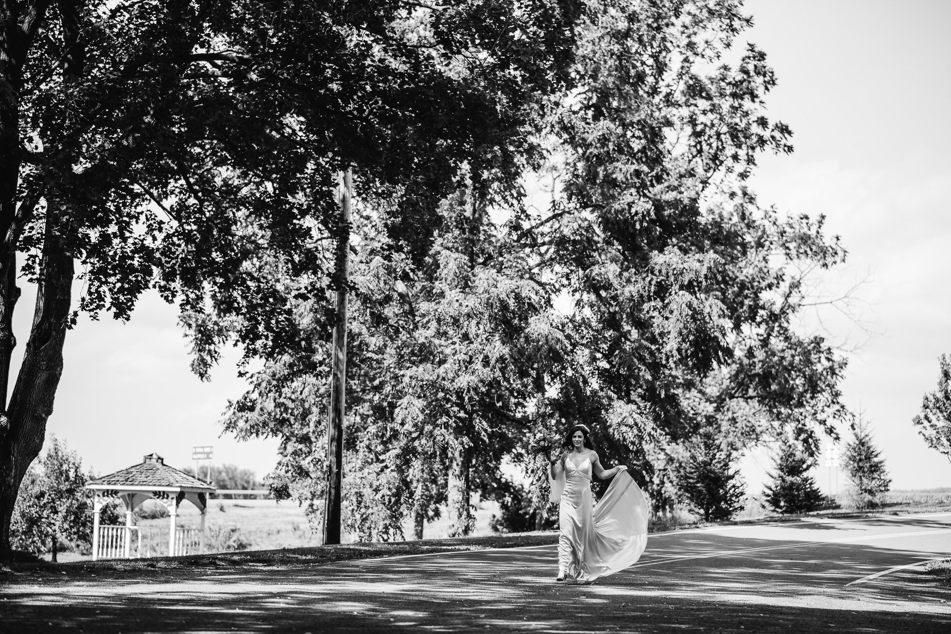 bride walking to first look at olde tater barn wedding in central bridge, ny photographed by traverse the tides