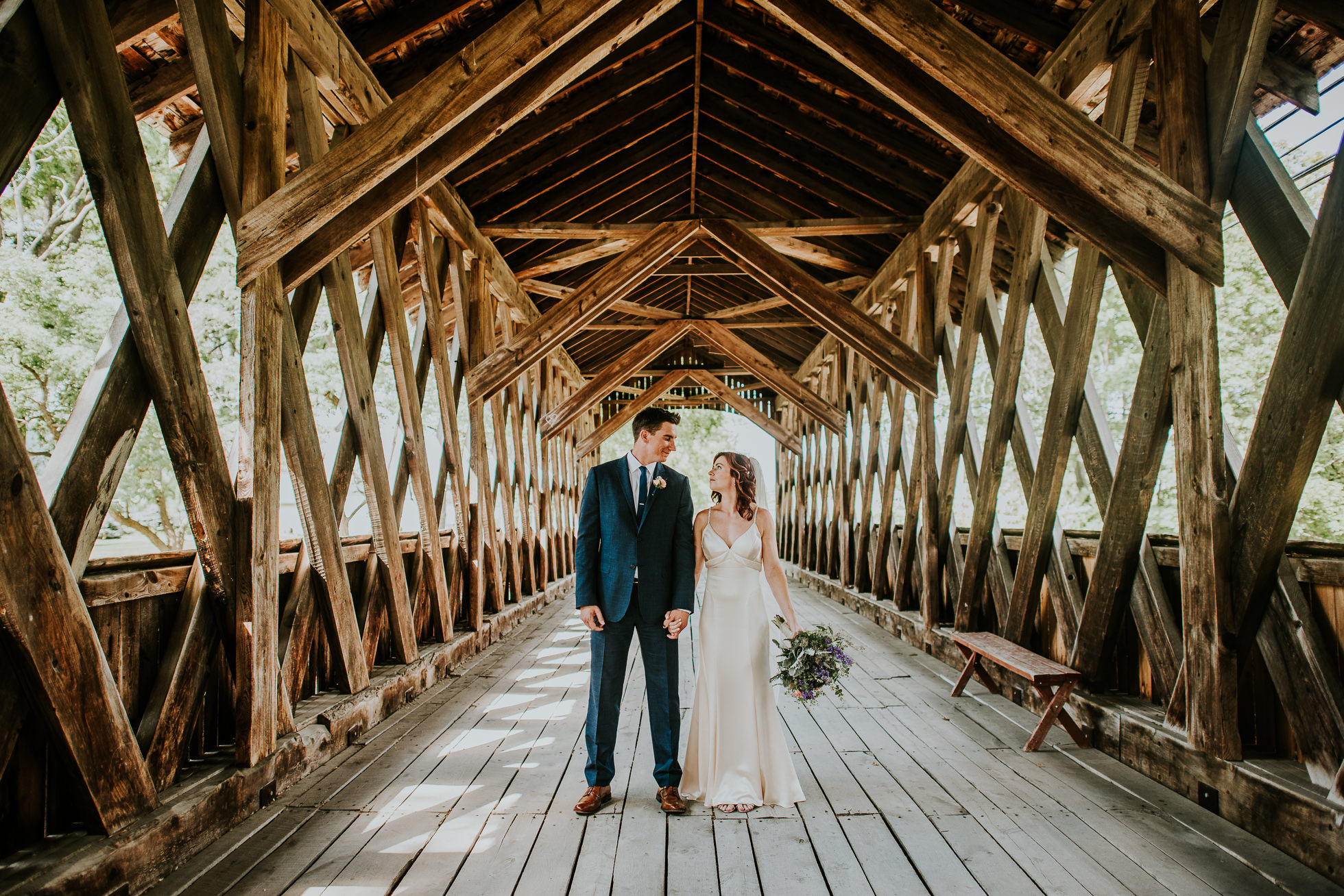 bride and groom portrait on bridge at olde tater barn wedding in central bridge, ny photographed by traverse the tides