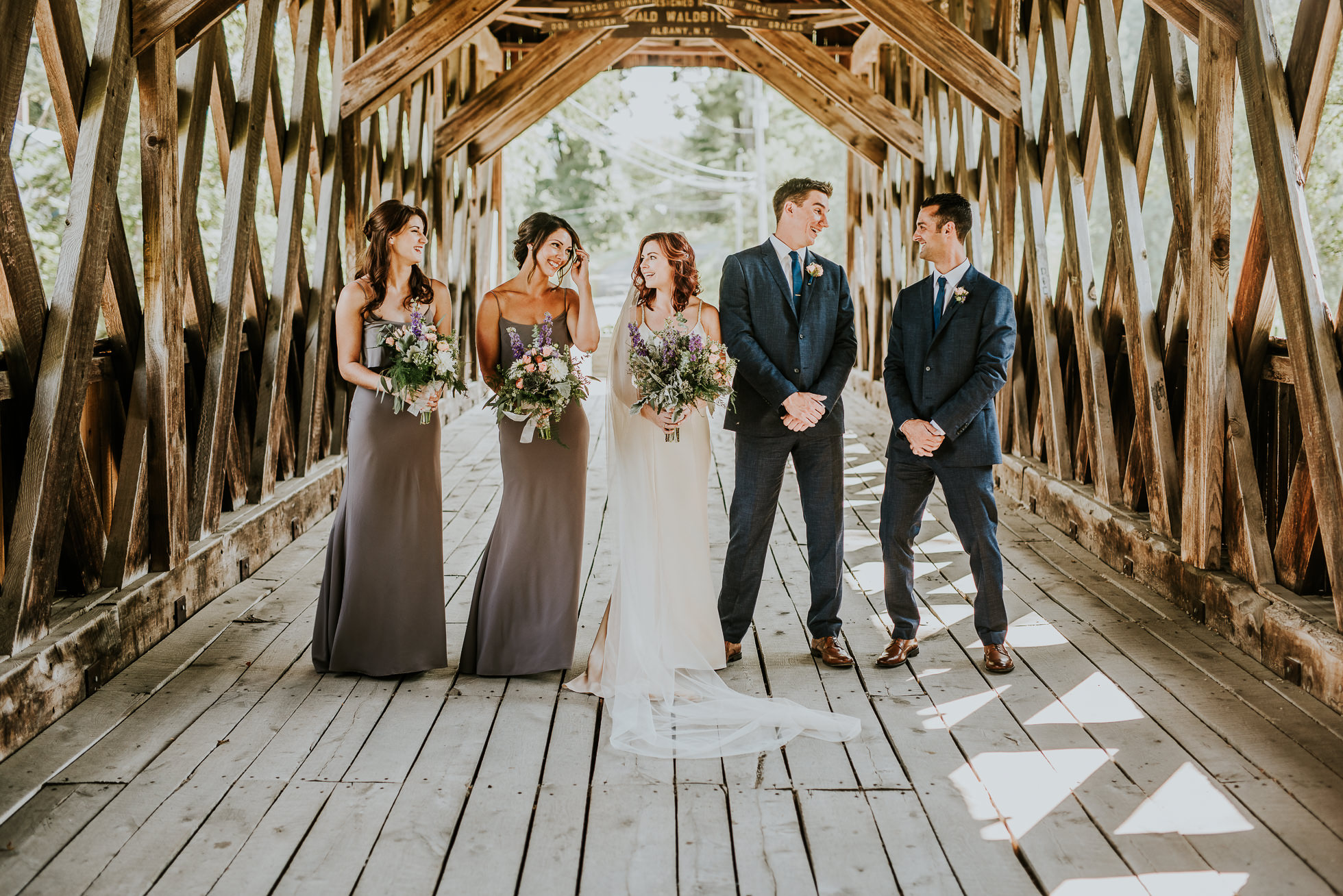 bridal party on bridge at olde tater barn wedding in central bridge, ny photographed by traverse the tides