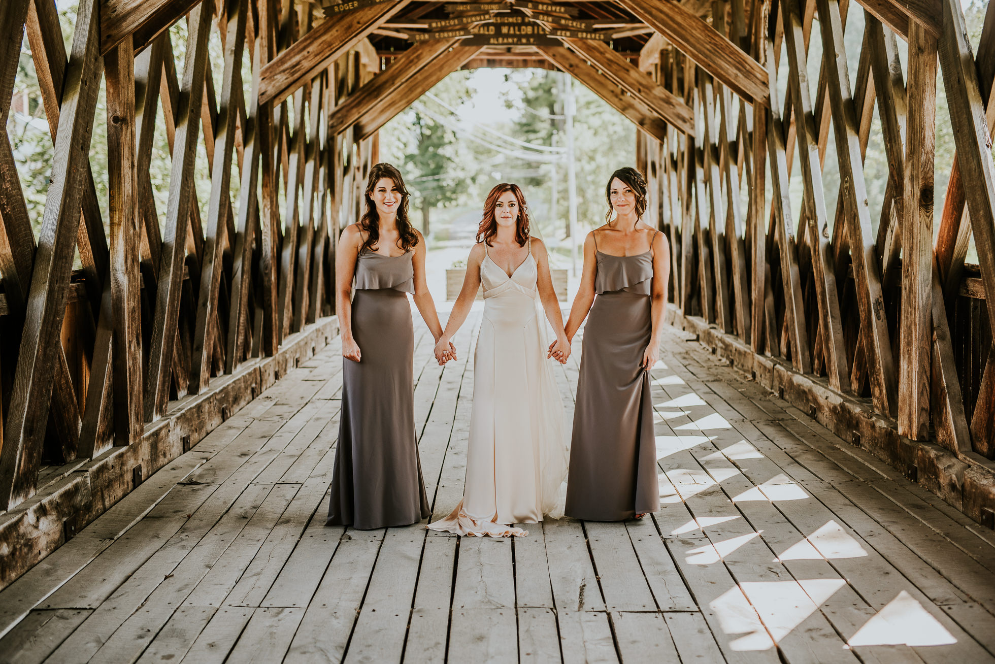 bride and bridesmaids on bridge at olde tater barn wedding in central bridge, ny photographed by traverse the tides