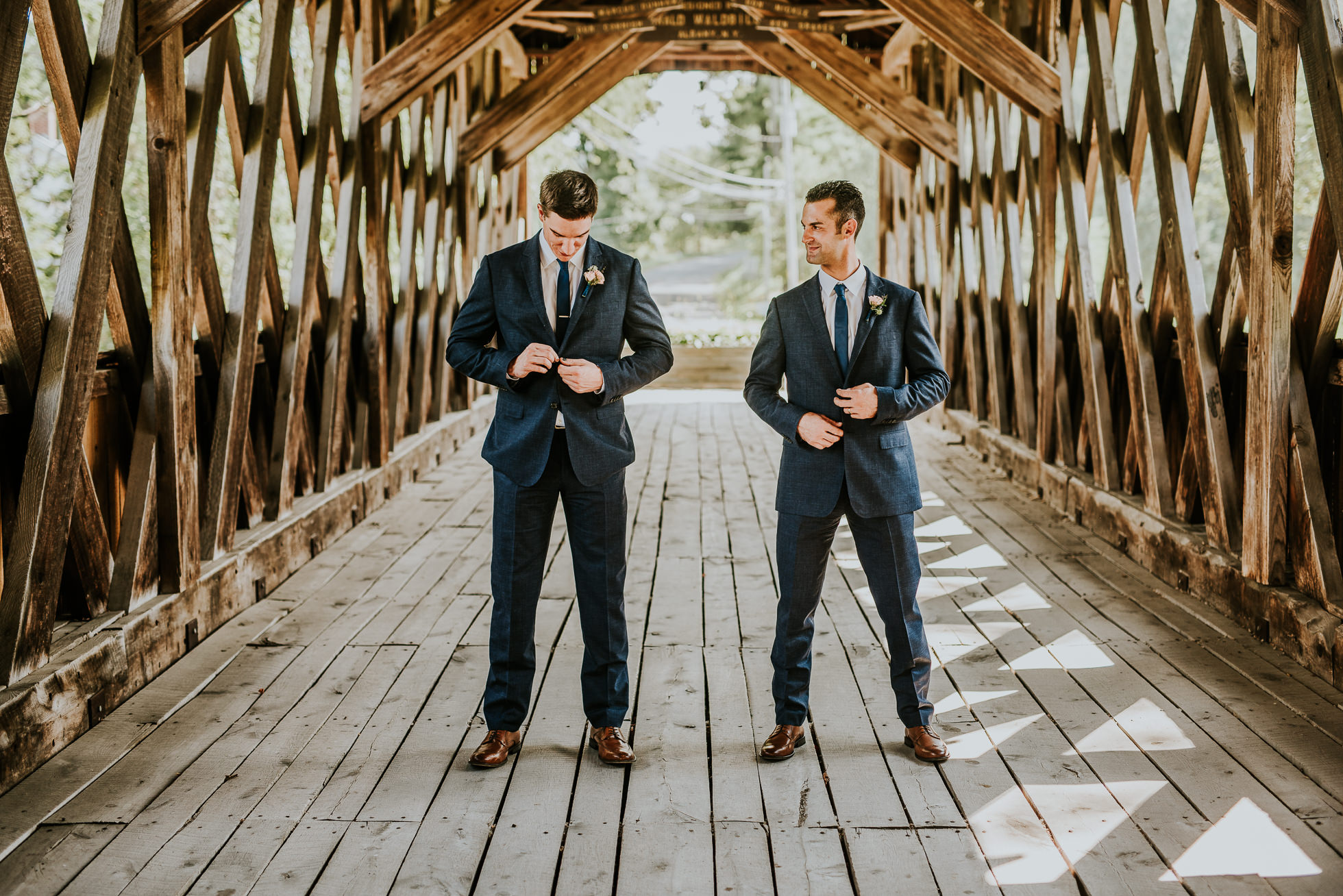 groom and best man on bridge at olde tater barn wedding in central bridge, ny photographed by traverse the tides