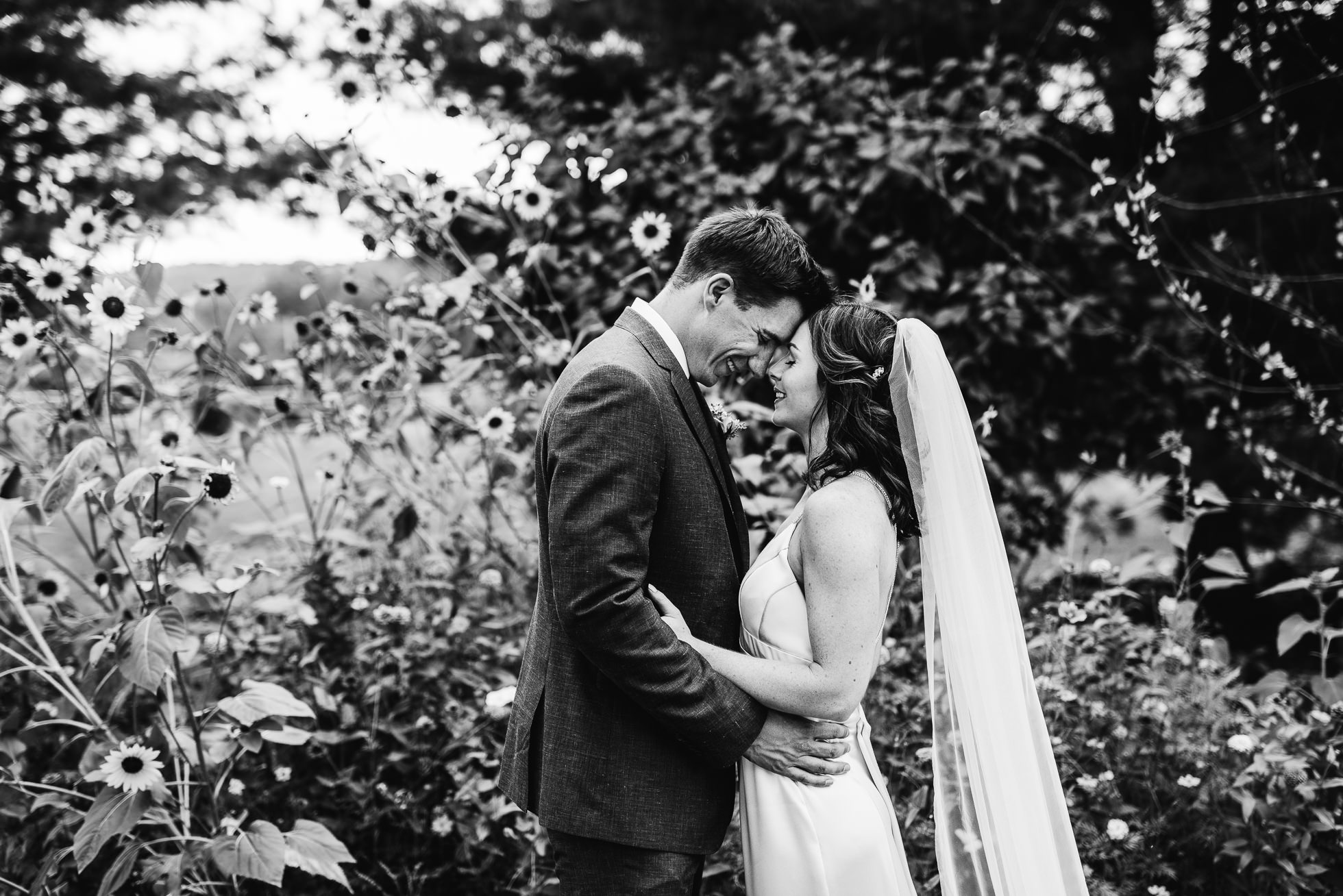 black and white wedding portraits by flowers at olde tater barn wedding in central bridge, ny photographed by traverse the tides
