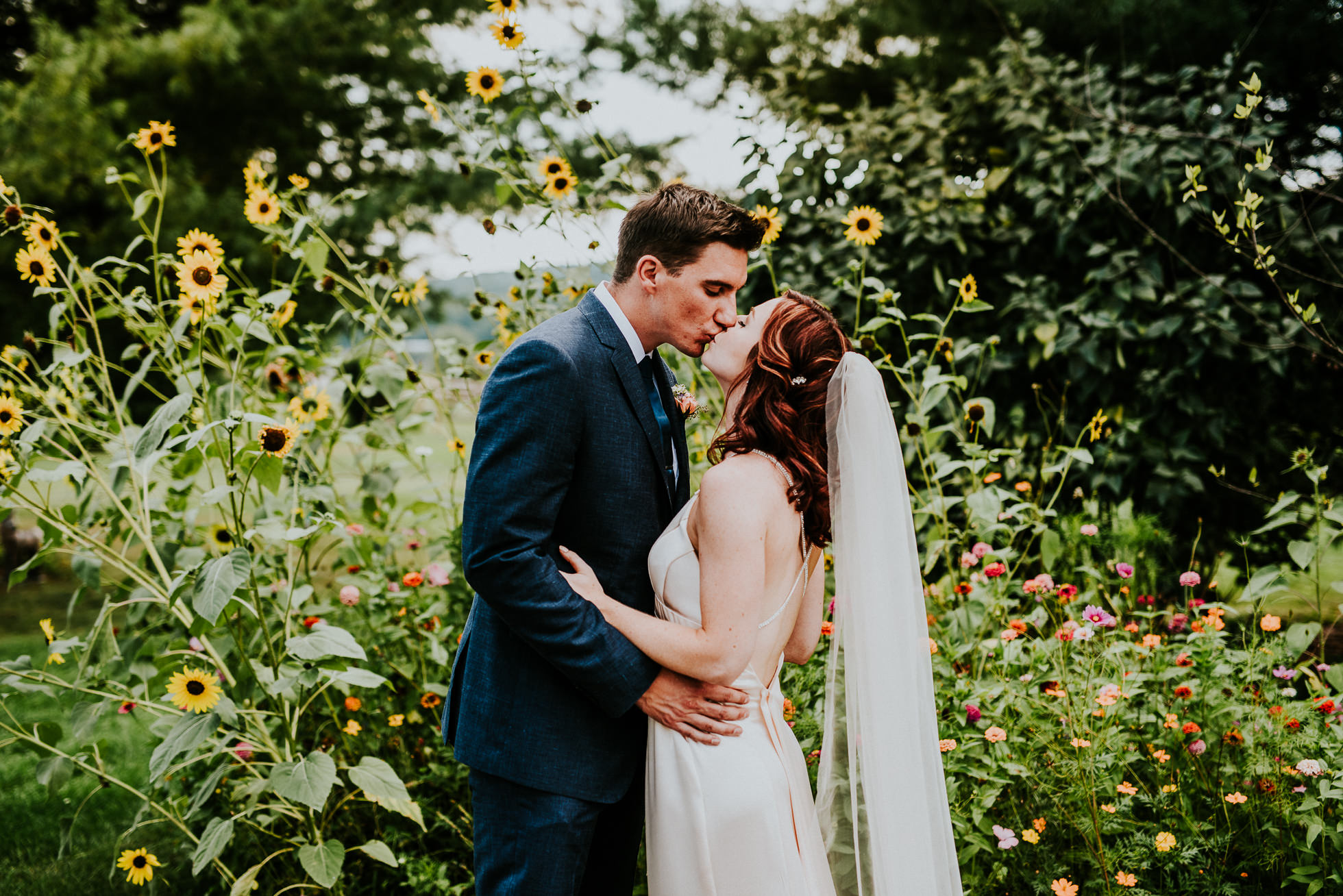 bride and groom kissing by flowers at olde tater barn wedding in central bridge, ny photographed by traverse the tides