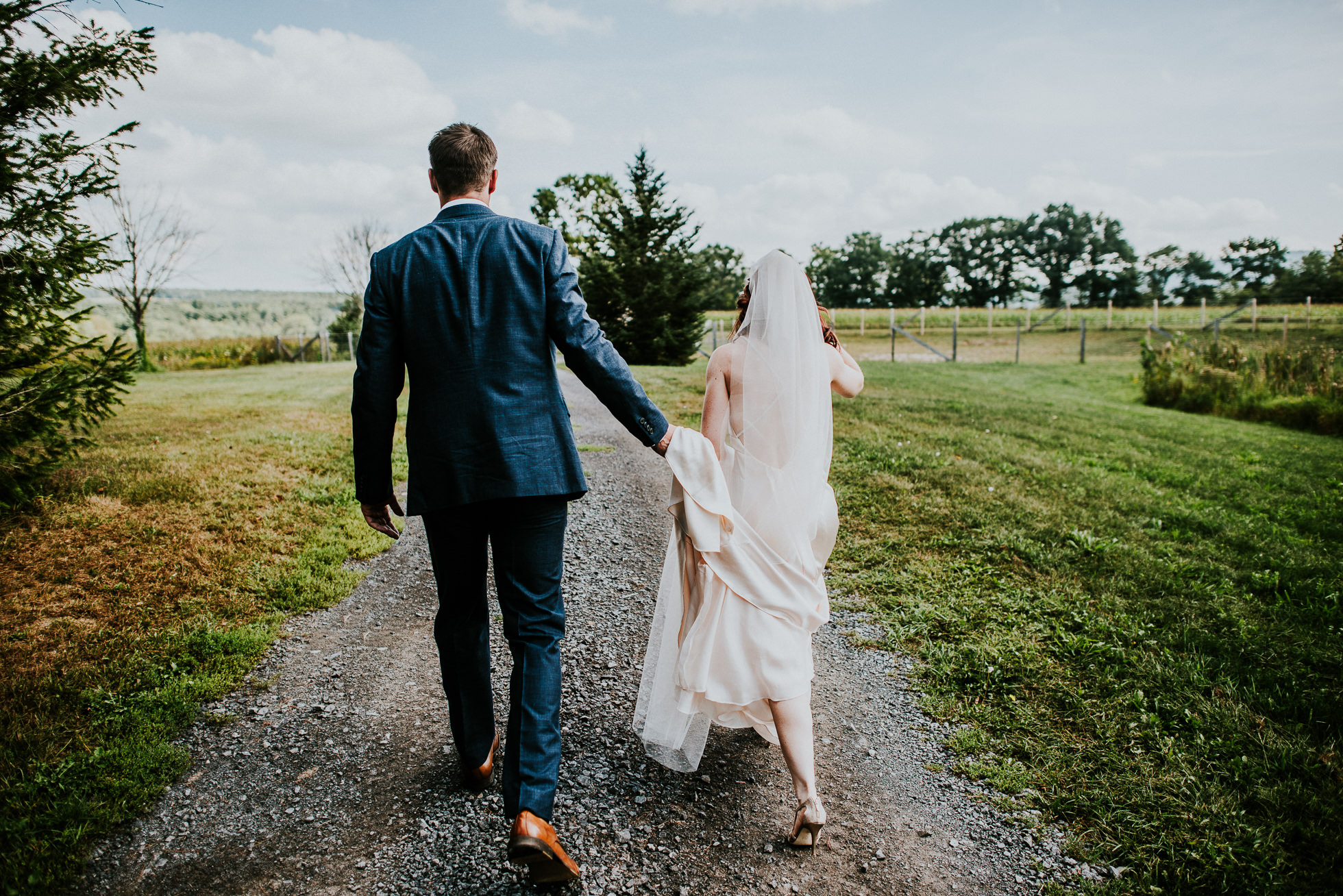 bride and groom walking at olde tater barn wedding in central bridge, ny photographed by traverse the tides