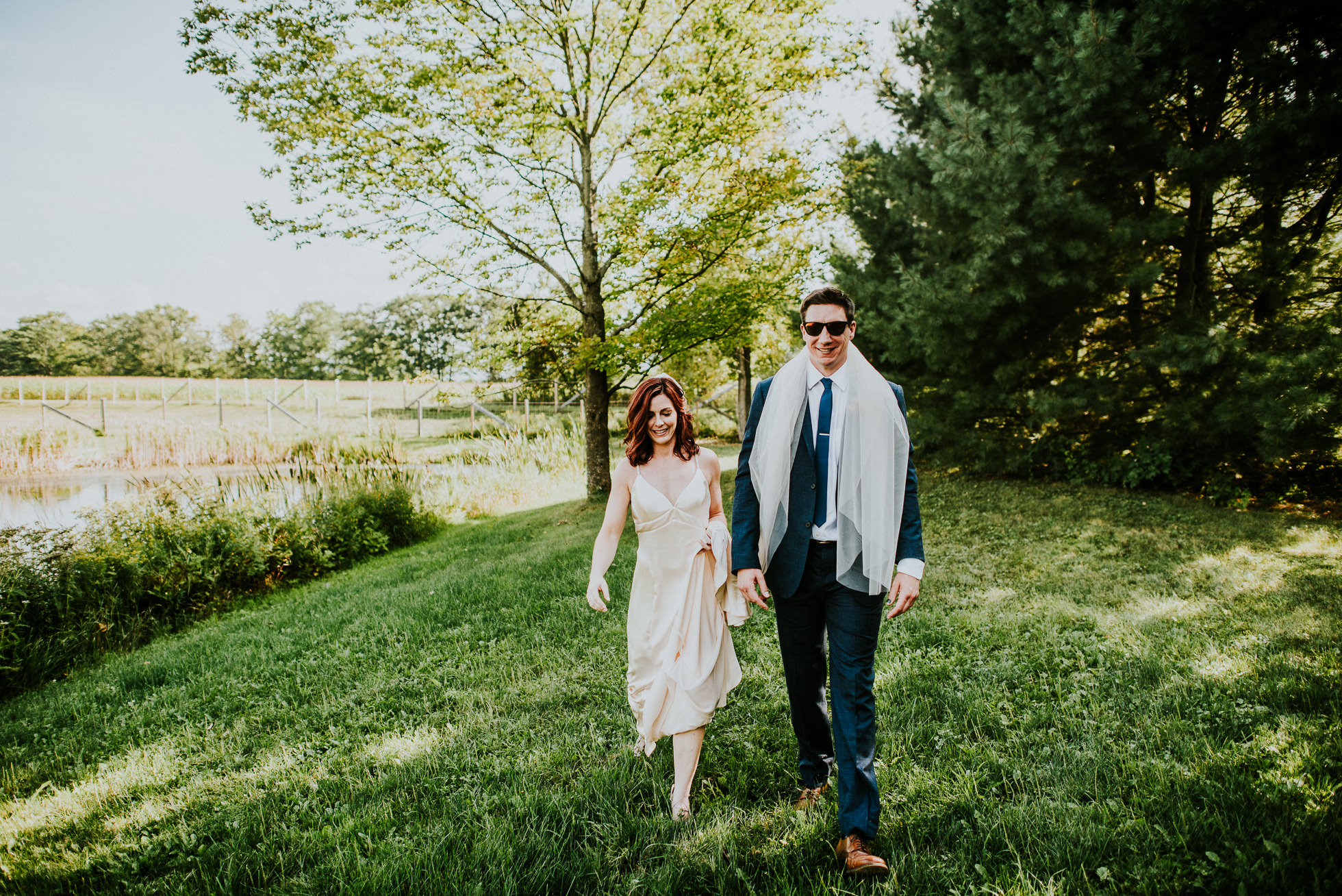 bride and groom walking to ceremony at olde tater barn wedding in central bridge, ny photographed by traverse the tides
