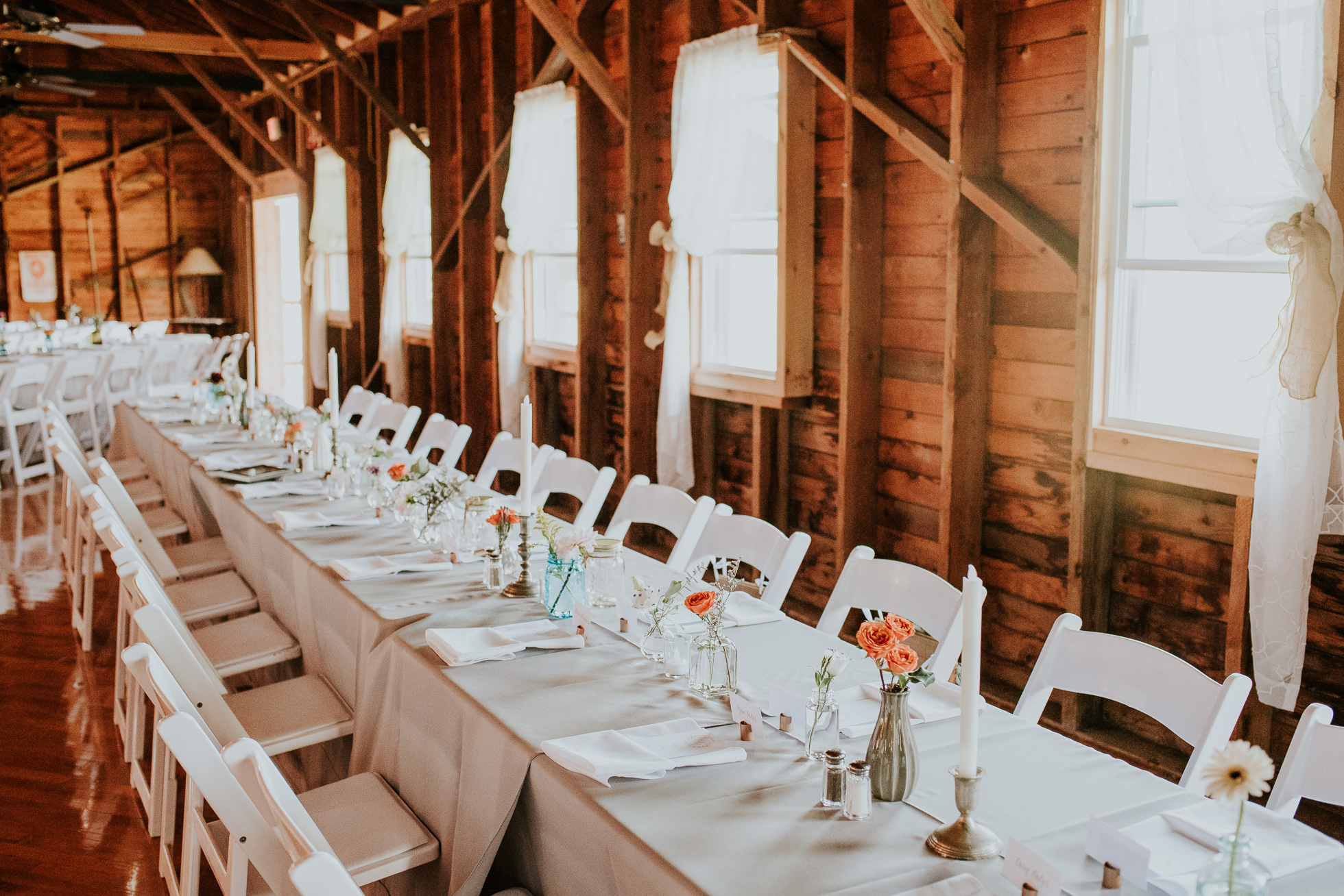 barn reception tables at olde tater barn wedding in central bridge, ny photographed by traverse the tides