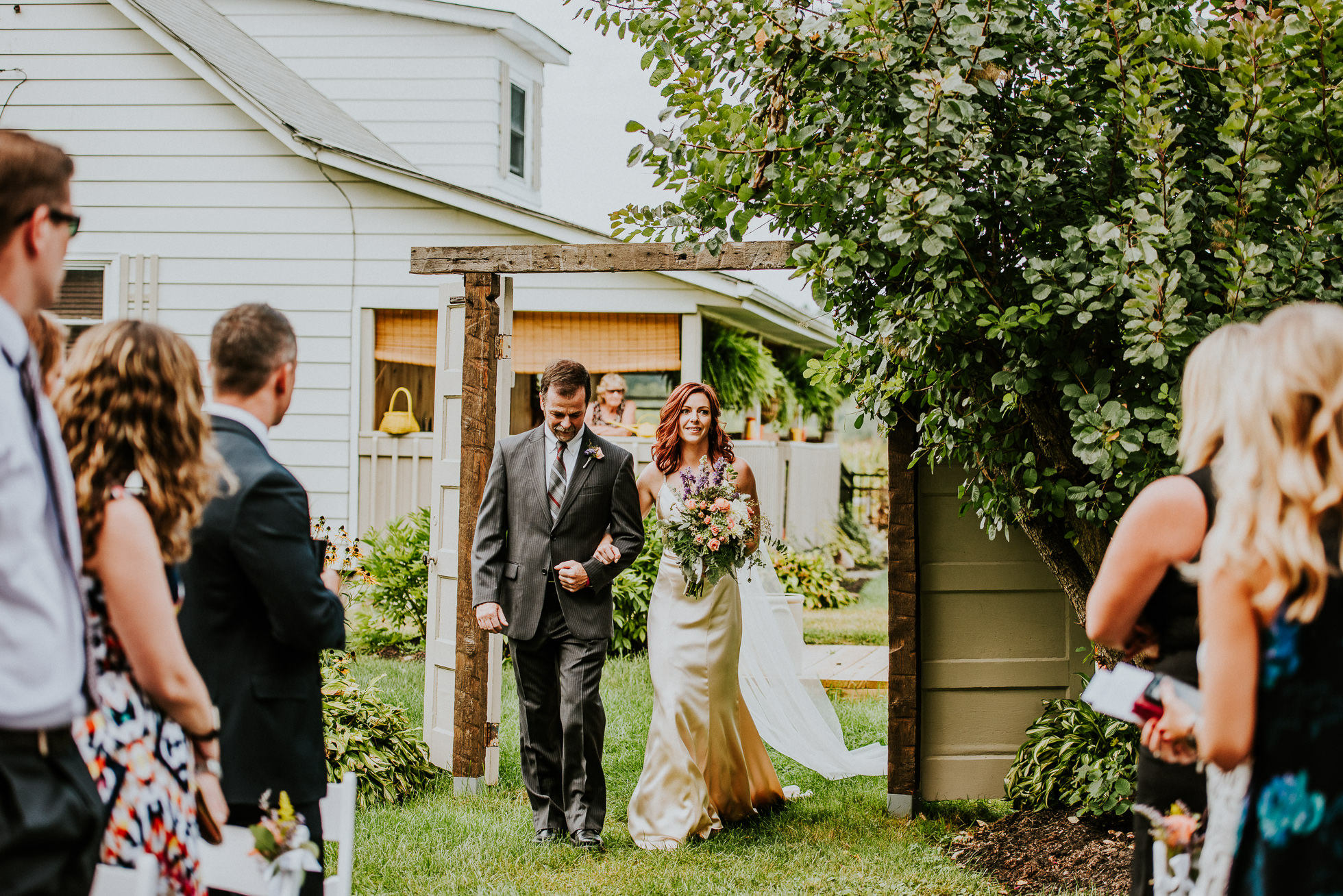 bride entering outdoor ceremony at olde tater barn wedding in central bridge, ny photographed by traverse the tides