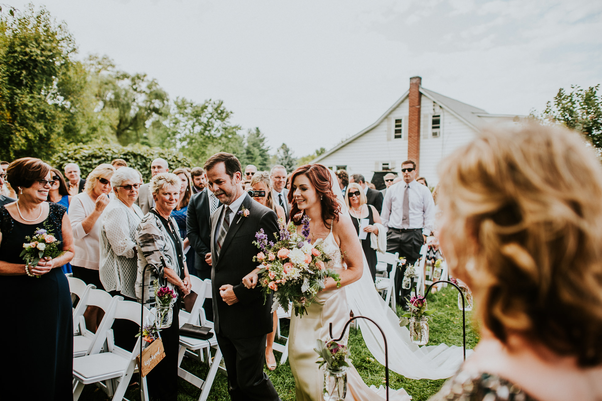 bride walking down aisle at outdoor ceremony at olde tater barn wedding in central bridge, ny photographed by traverse the tides