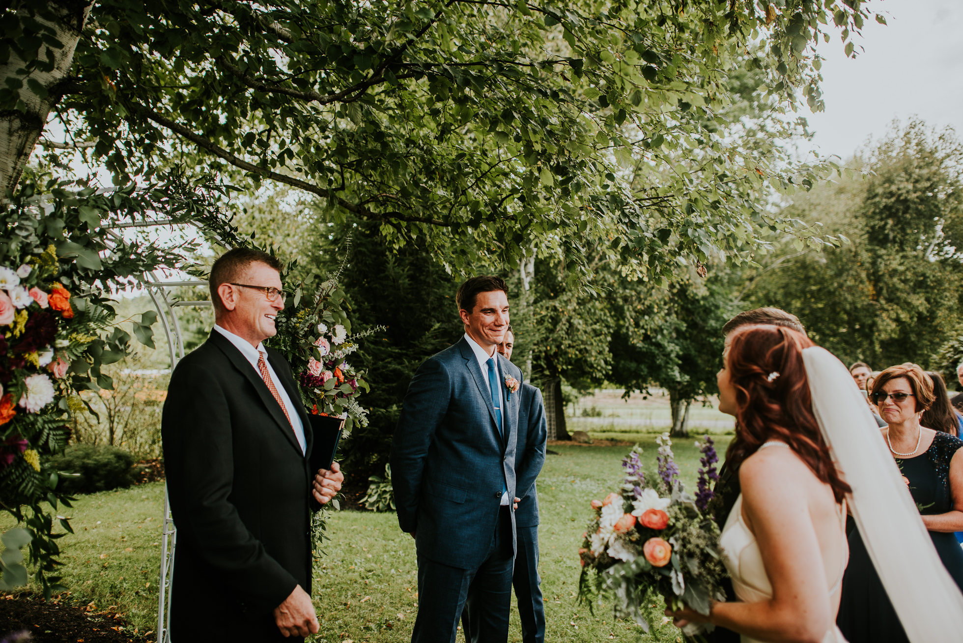 grooms sees bride for the first time at outdoor ceremony at olde tater barn wedding in central bridge, ny photographed by traverse the tides