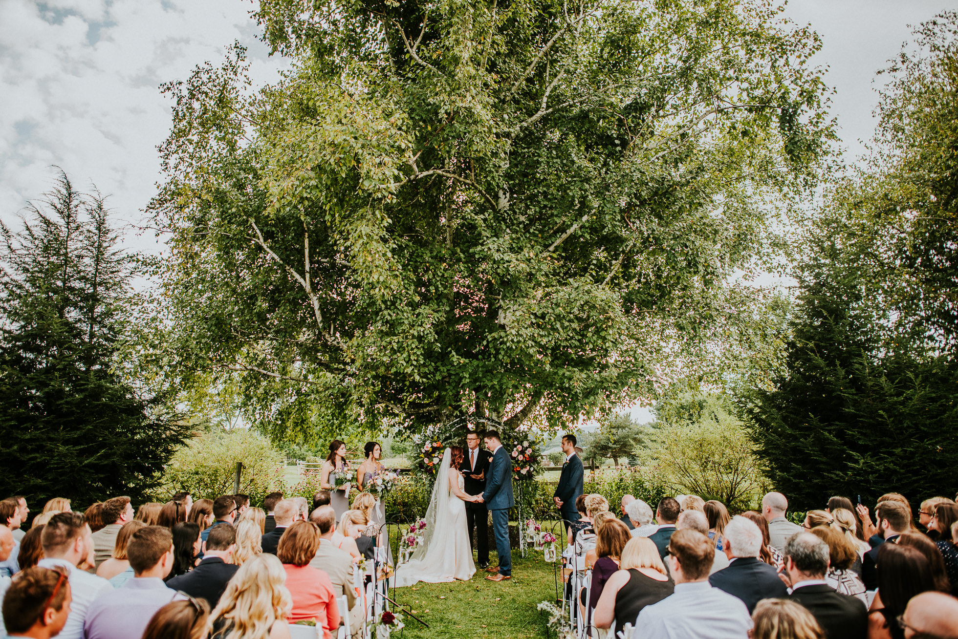 rustic outdoor ceremony at olde tater barn wedding photographed by traverse the tides