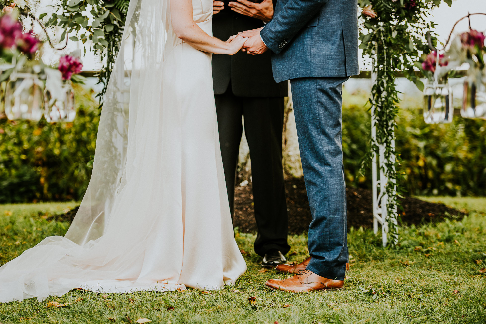 bride and groom hold hands at rustic outdoor ceremony at olde tater barn wedding in central bridge, ny photographed by traverse the tides