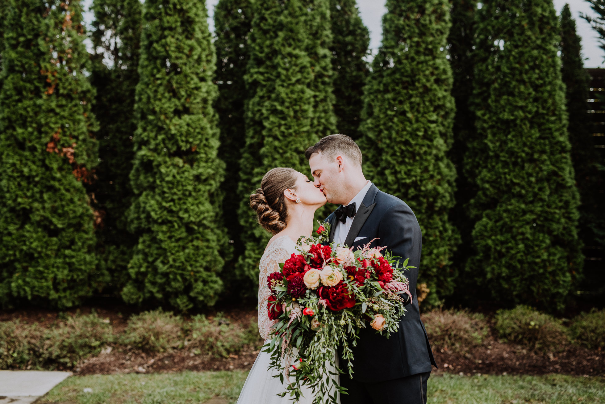 bride and groom kissing and holding bouquet the cordelle nashville