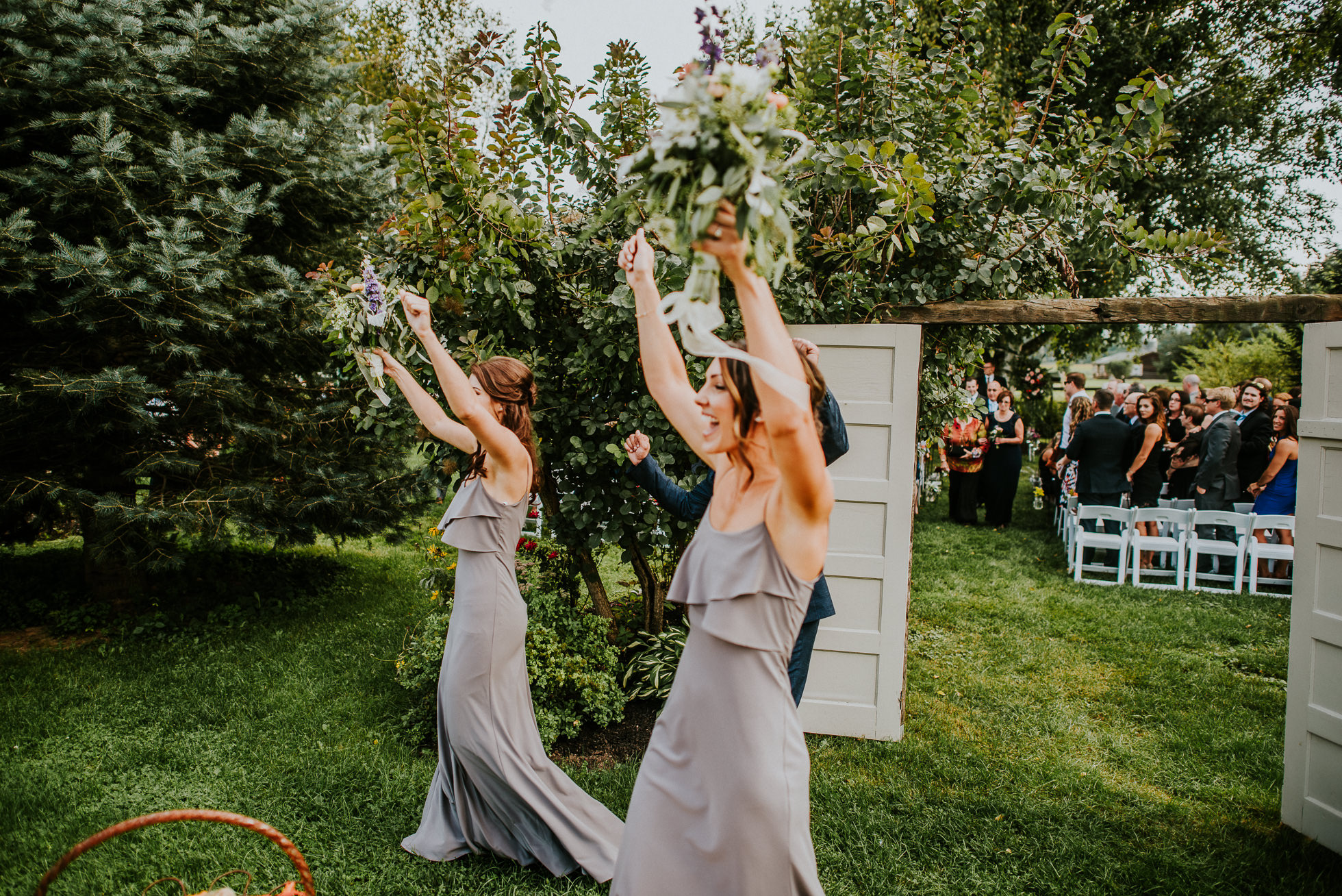 bridesmaids celebrate at rustic outdoor ceremony at olde tater barn wedding in central bridge, ny photographed by traverse the tides