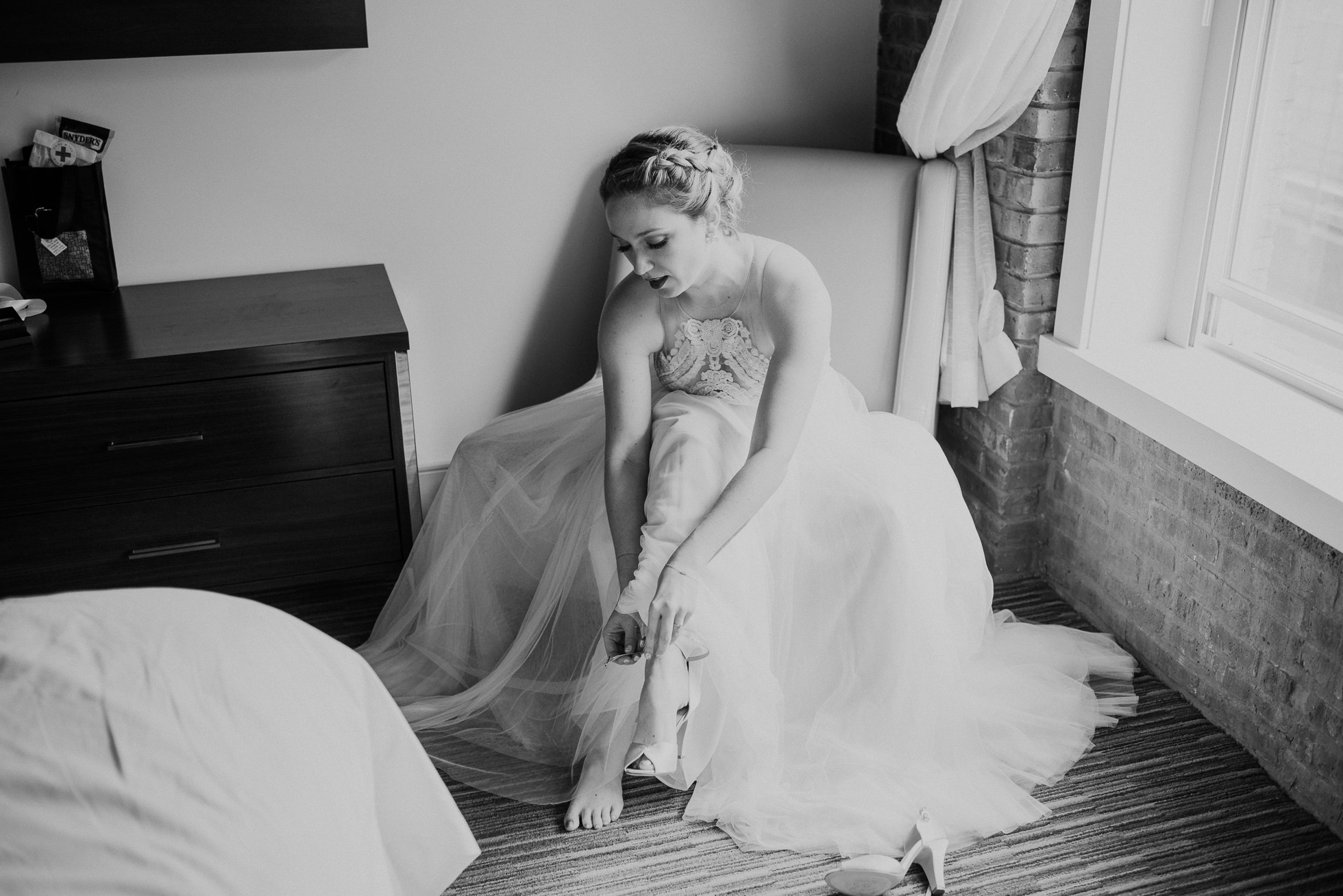 bride putting on shoes photographed by Traverse The Tides