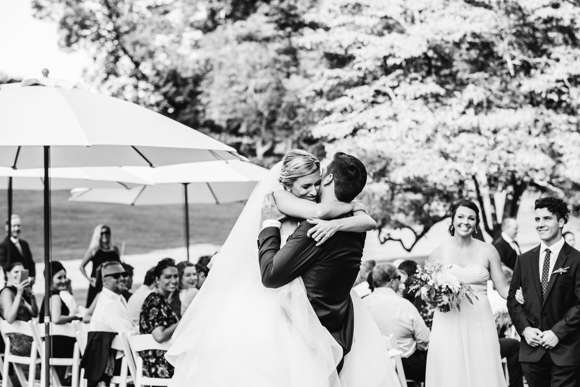 bride and groom hug at wedding ceremony at lyndhurst castle photographed by traverse the tides