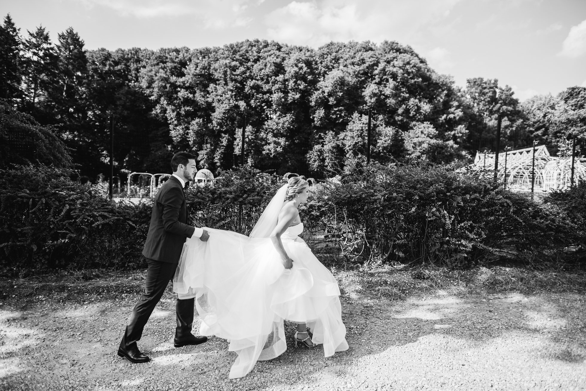 bride and groom walking at lyndhurst castle rose garden photographed by traverse the tides