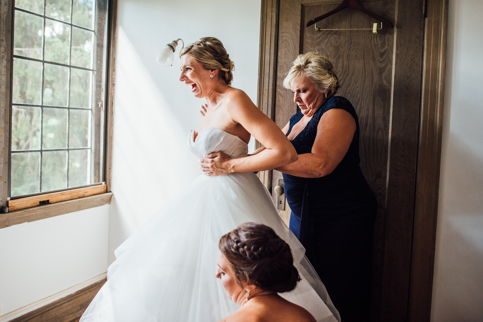 bride putting dress on with mom and sister at lyndhurst castle photographed by traverse the tides-2