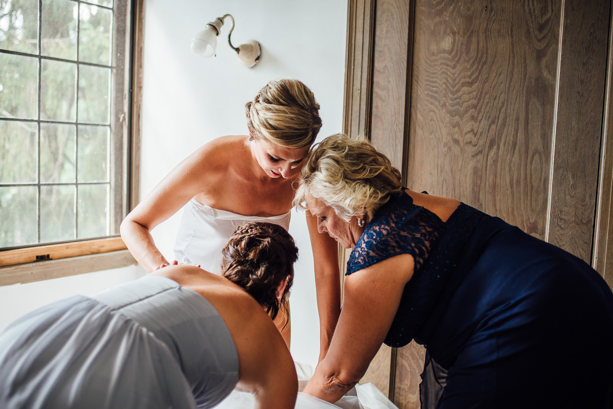 bride putting dress on with mom and sister at lyndhurst castle photographed by traverse the tides