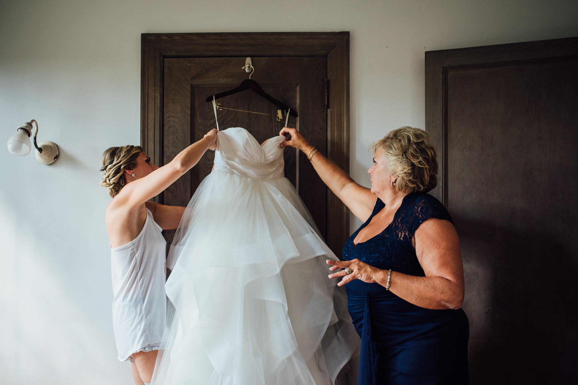 bride putting dress on with mom at lyndhurst castle photographed by traverse the tides