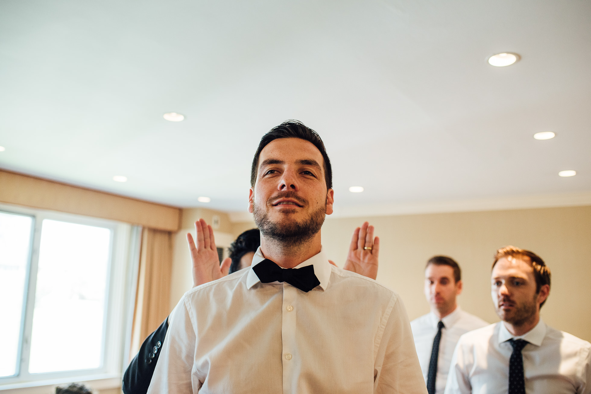 groom putting on bowtie at lyndhurst castle wedding photographed by traverse the tides