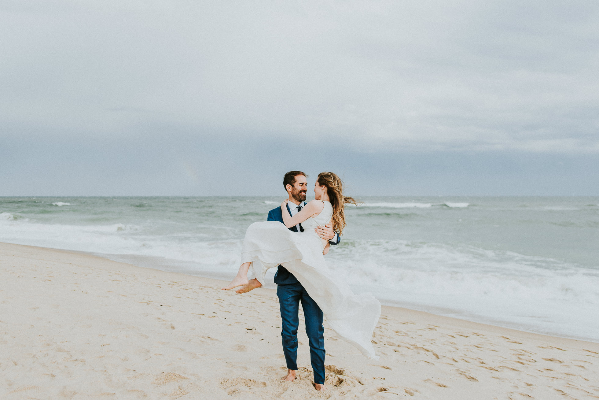 happy groom carrying bride at beach Montauk wedding photographed by Traverse the Tides