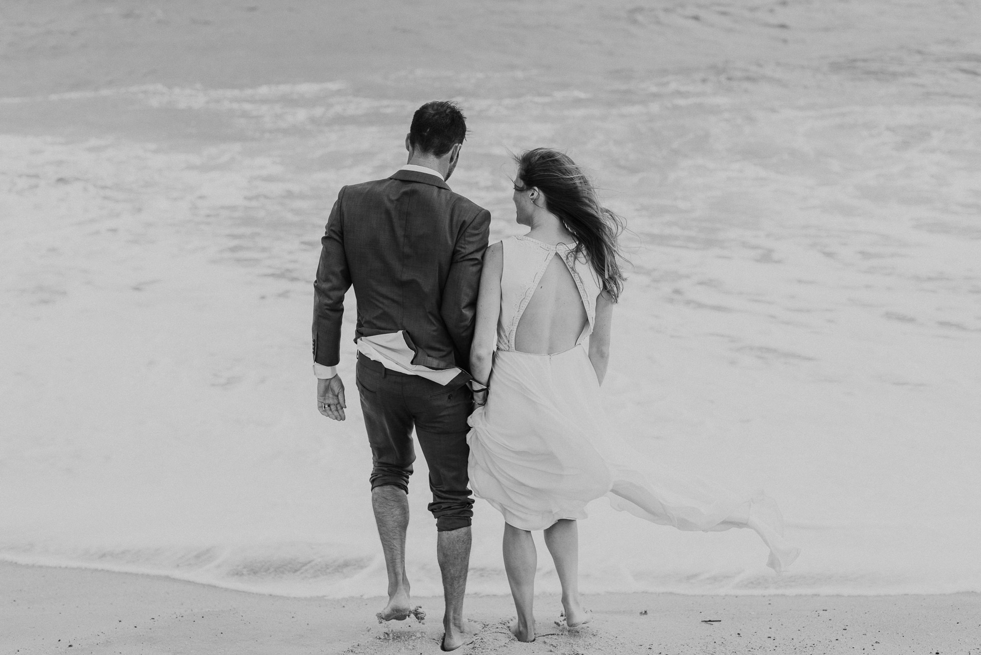 bride and groom going into the water at beach Montauk wedding photographed by Traverse the Tides
