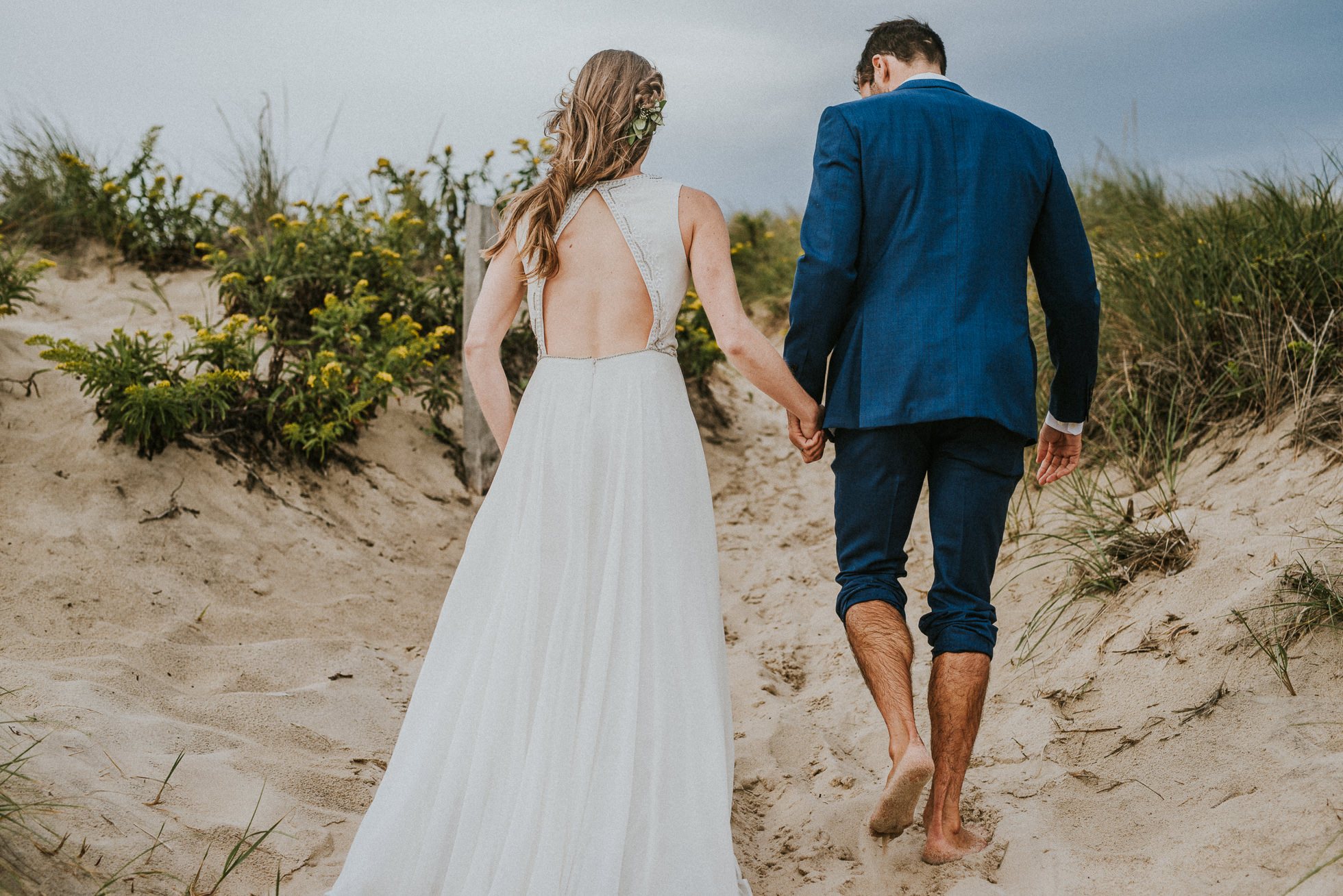 bride and groom walking hand in hand Montauk wedding photographed by Traverse the Tides