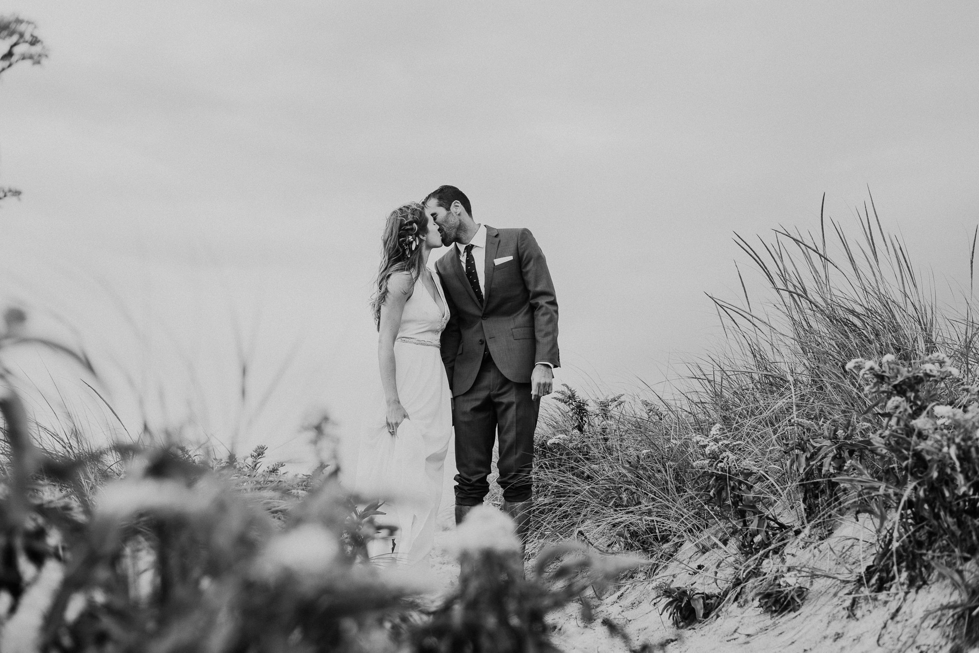 bride and groom kissing in the sand dunes Montauk wedding photographed by Traverse the Tides