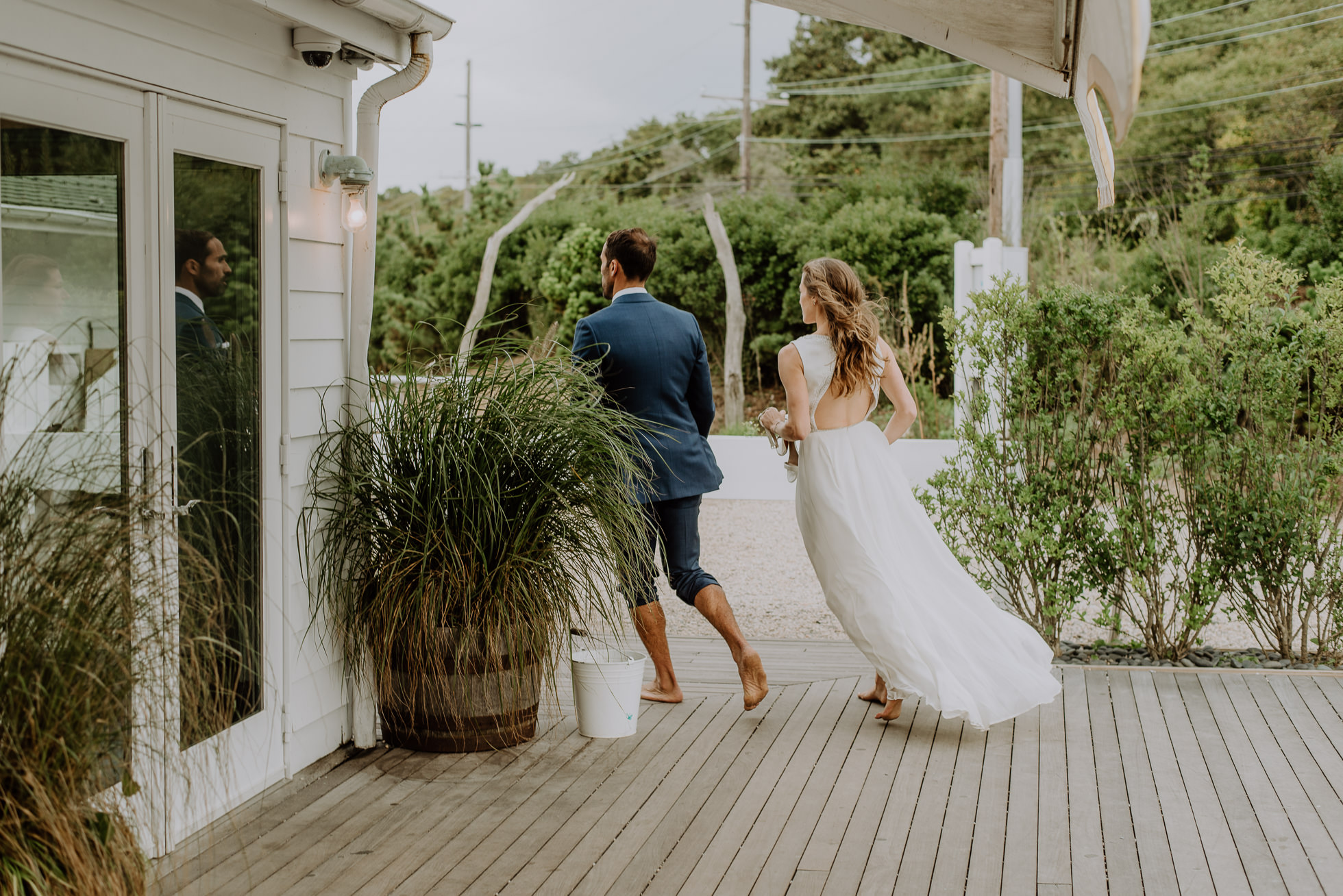 bride and groom returning to reception at the surf lodge in Montauk wedding photographed by Traverse the Tides