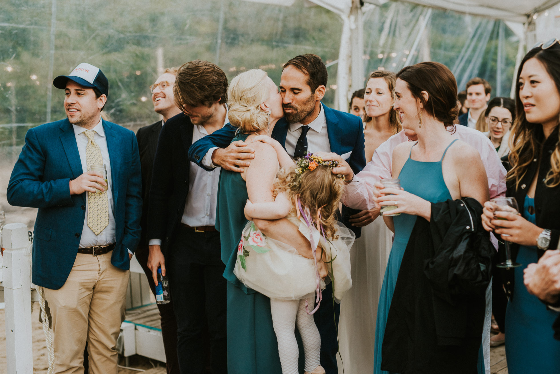 bride and groom kissing maid of honor at the surf lodge in Montauk wedding photographed by Traverse the Tides