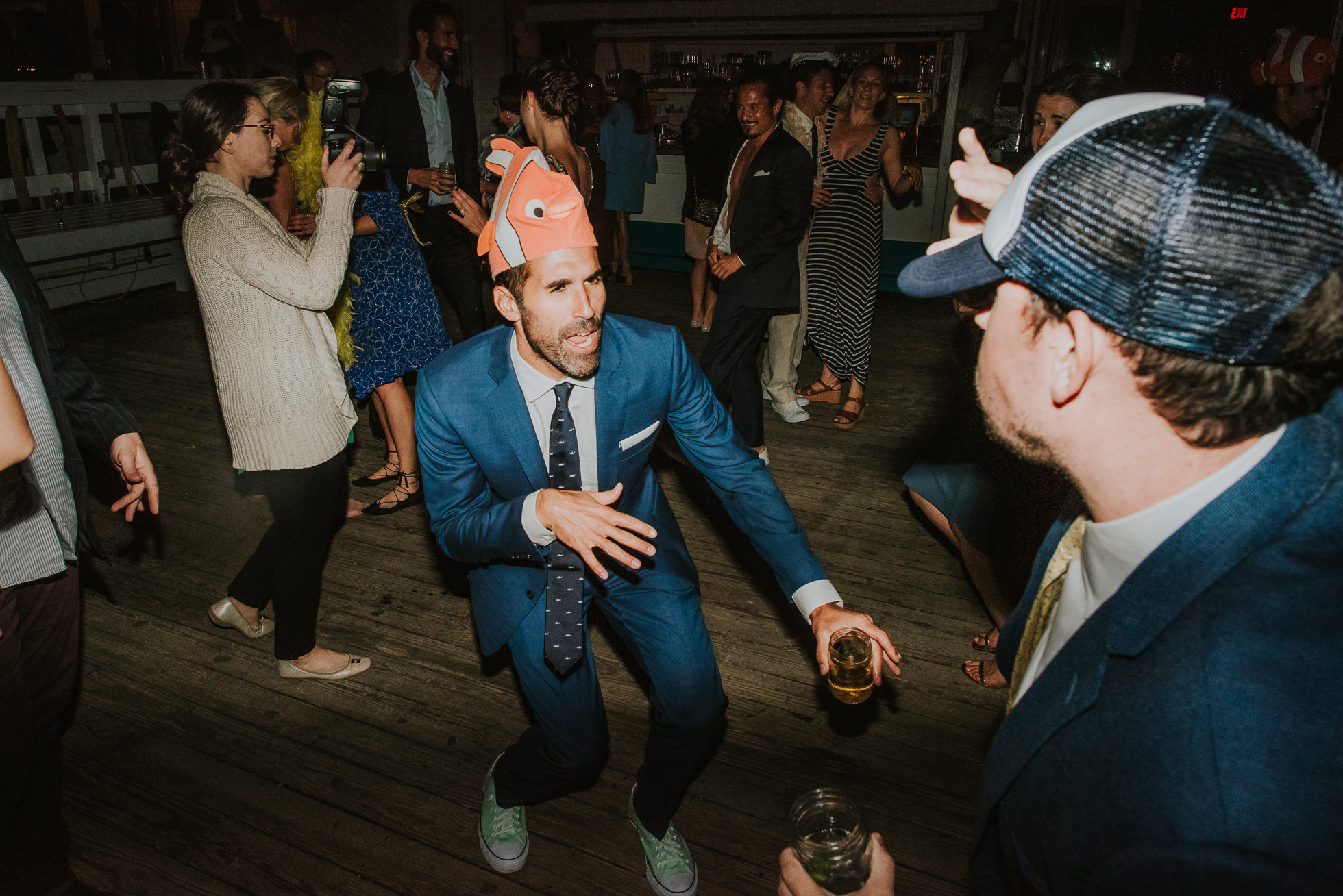 groom with funny hat at reception Montauk wedding photographed by Traverse the Tides