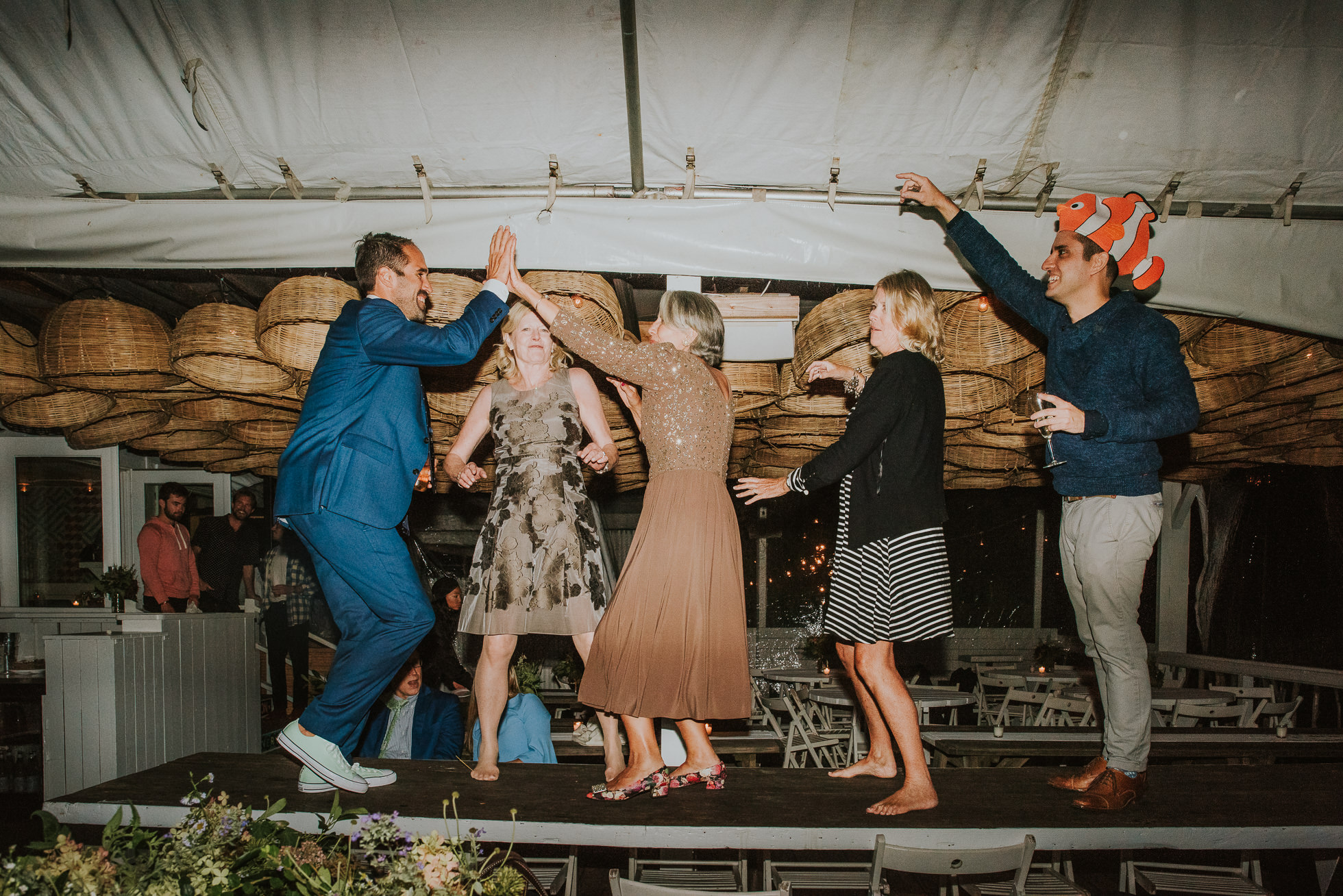 guests dancing on table at reception Montauk wedding photographed by Traverse the Tides
