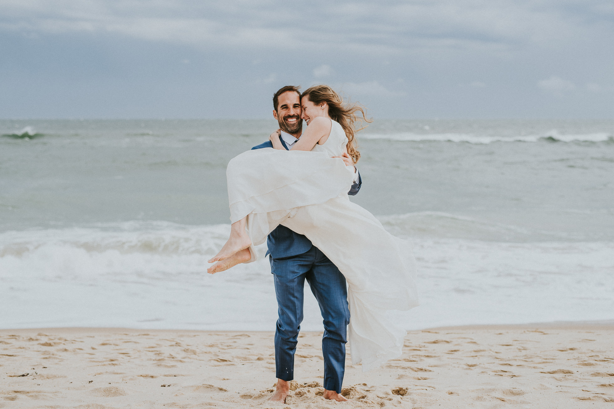 groom carrying bride at beach Montauk wedding photographed by Traverse the Tides