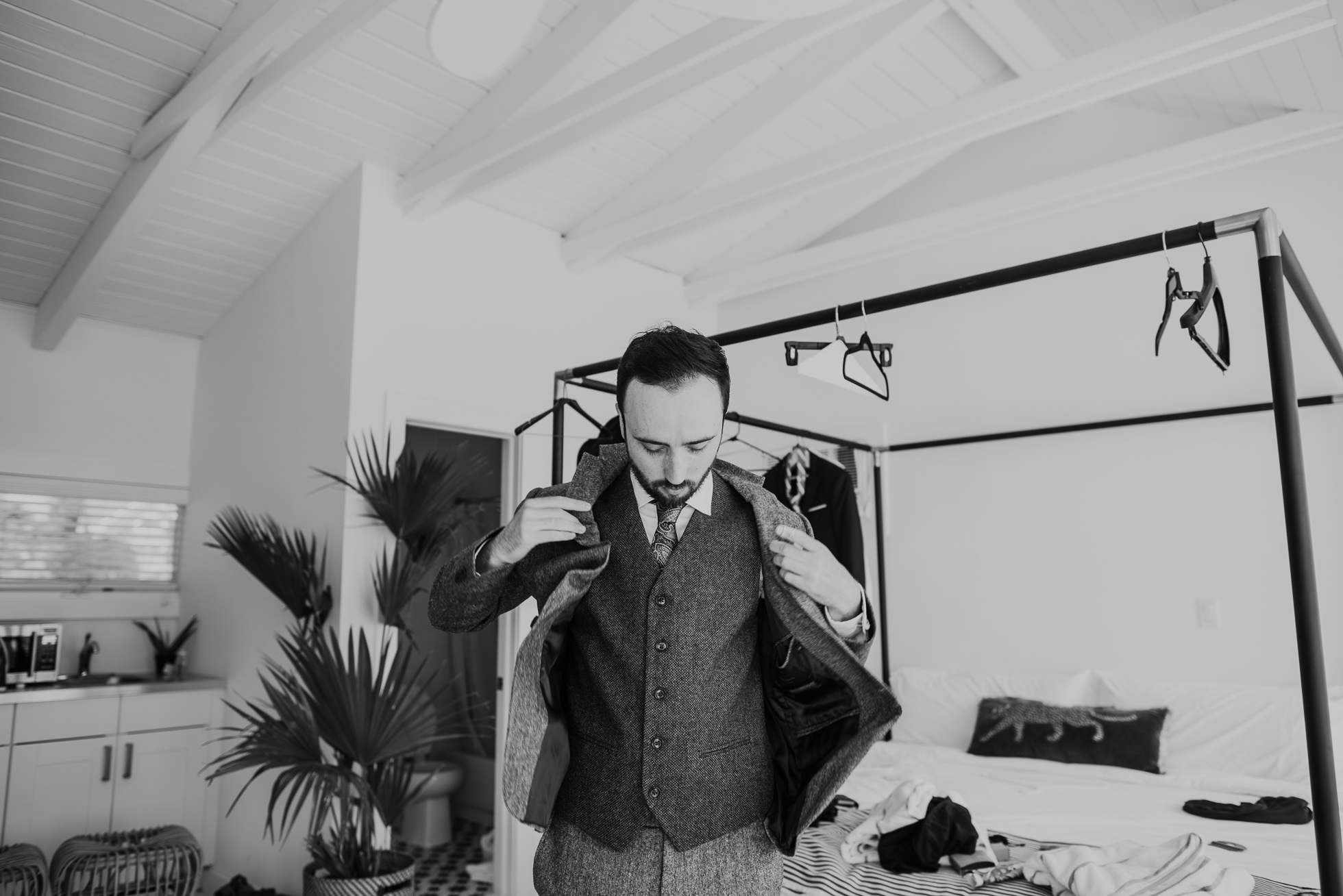groom putting on wool suit jacket